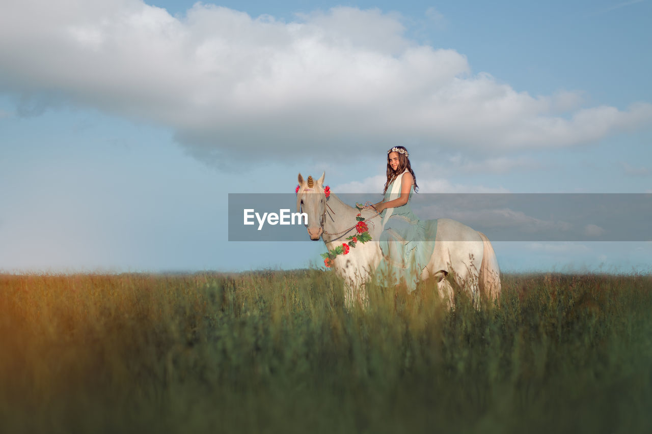 Girl Riding Horse On Field Against Sky