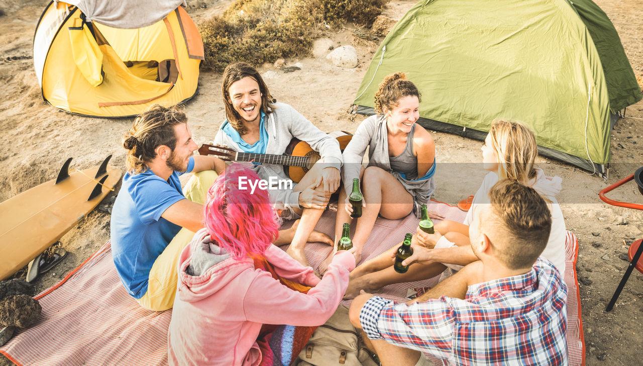 Friends enjoying by tents