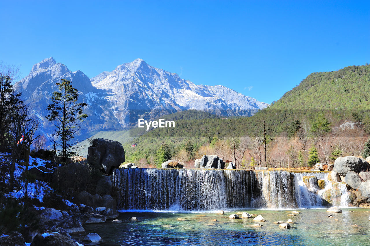 water, mountain, tranquil scene, nature, beauty in nature, scenics, blue, rock - object, day, waterfall, clear sky, tranquility, no people, motion, outdoors, sunlight, tree, mountain range, sky, cold temperature, winter, hot spring, mammal