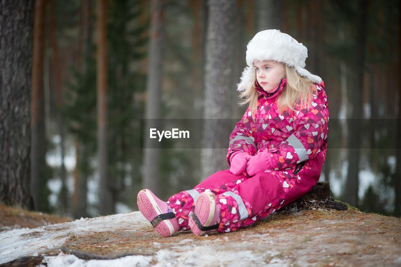 Girl Sitting On Tree Stump In Forest