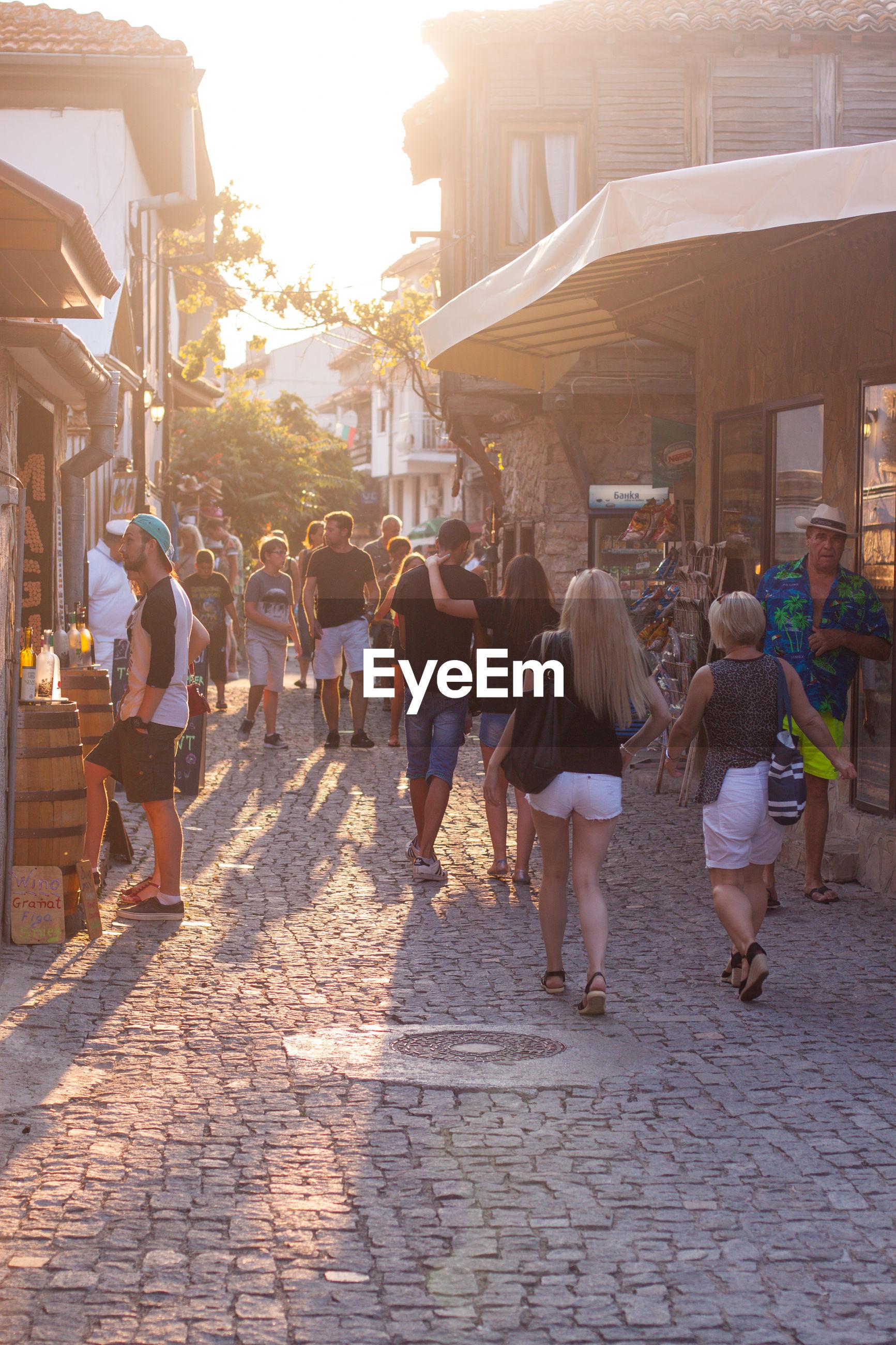 PEOPLE WALKING ON STREET IN CITY AGAINST SKY