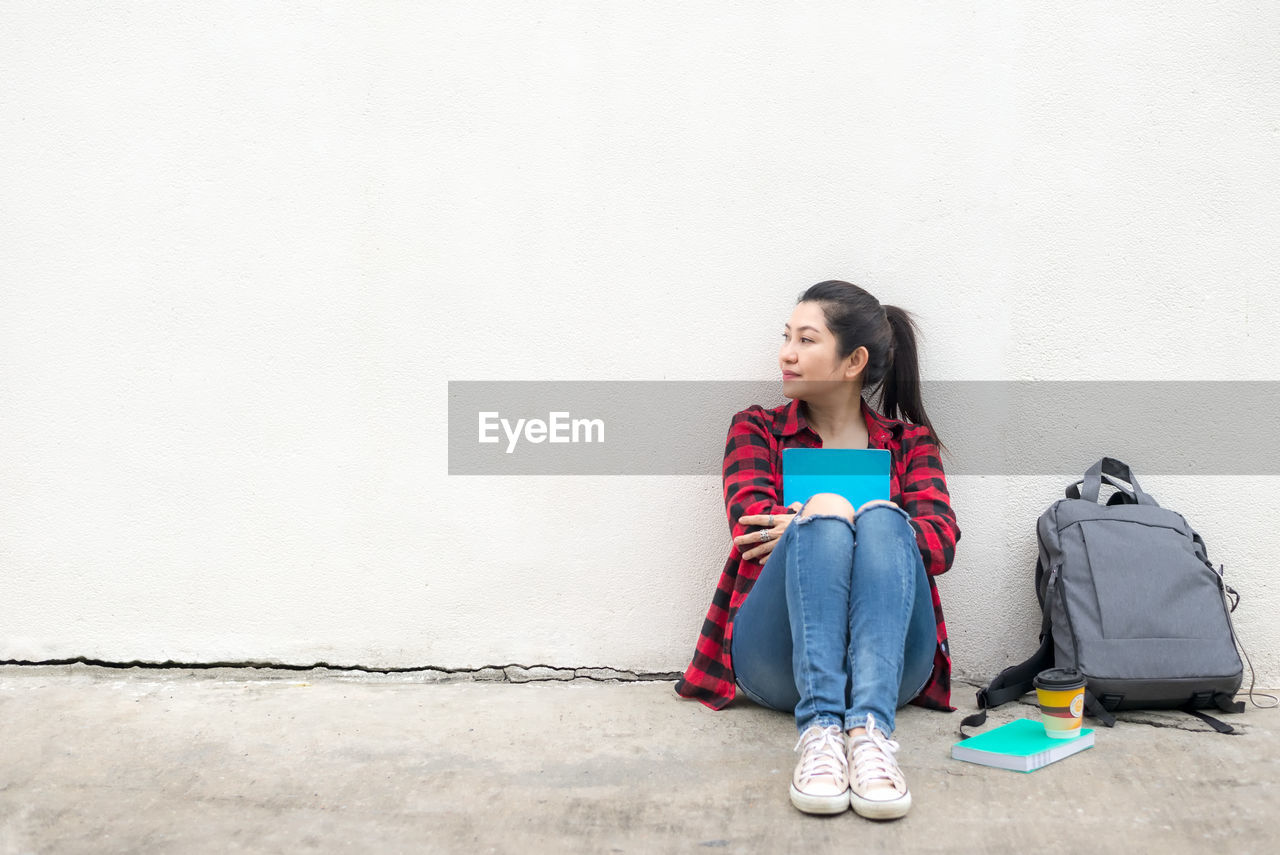 YOUNG WOMAN LOOKING AWAY WHILE SITTING AGAINST WALL
