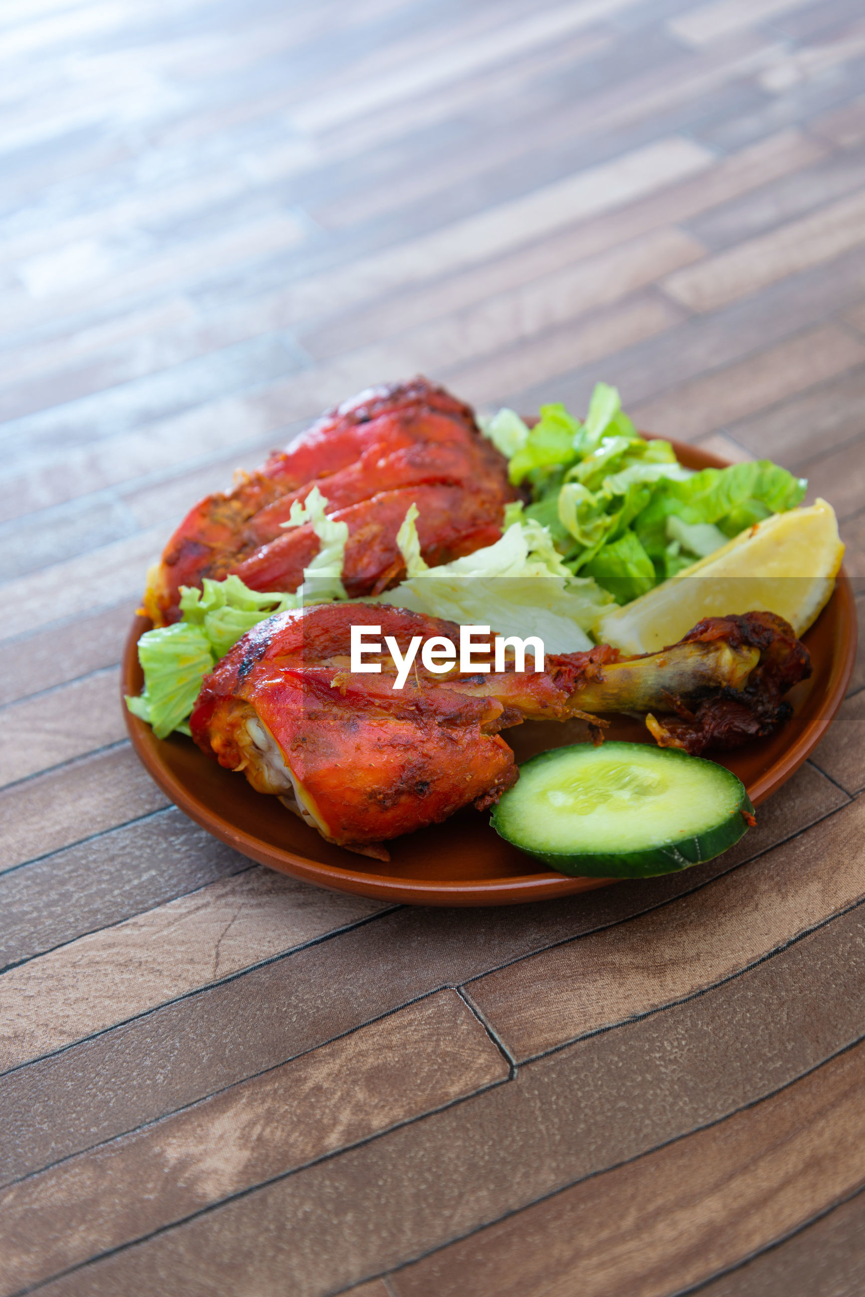High angle view of cooked chicken meat and salad in plate on table
