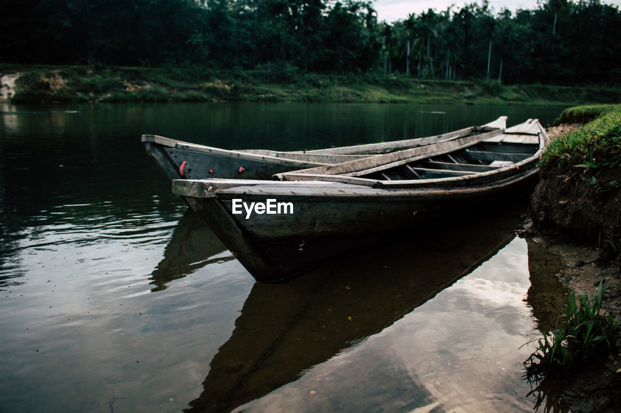 water, nautical vessel, mode of transportation, reflection, transportation, moored, day, no people, tranquility, nature, lake, rowboat, waterfront, plant, tree, abandoned, tranquil scene, outdoors, sinking, anchored