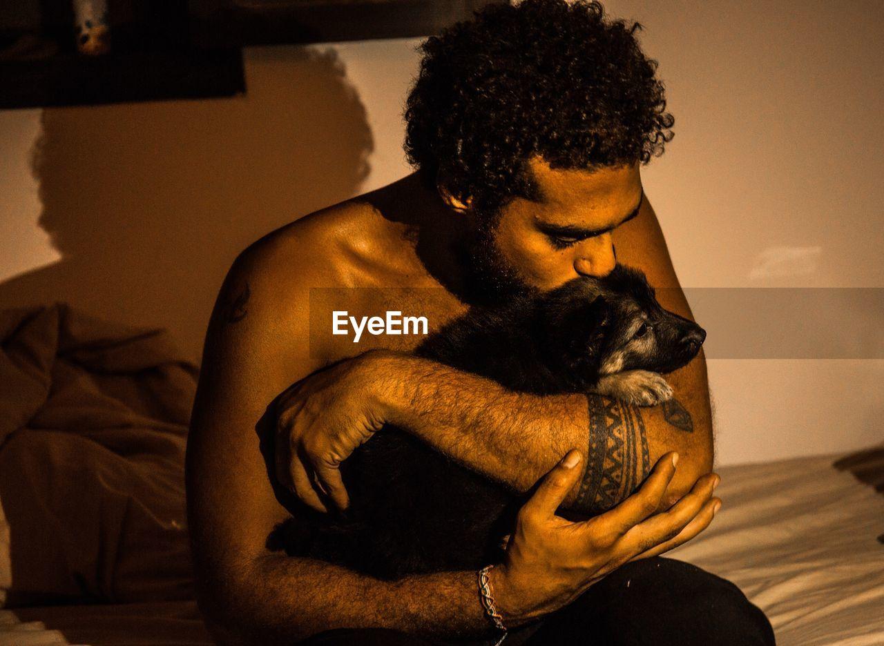 CLOSE-UP OF MAN AND DOG AT HOME