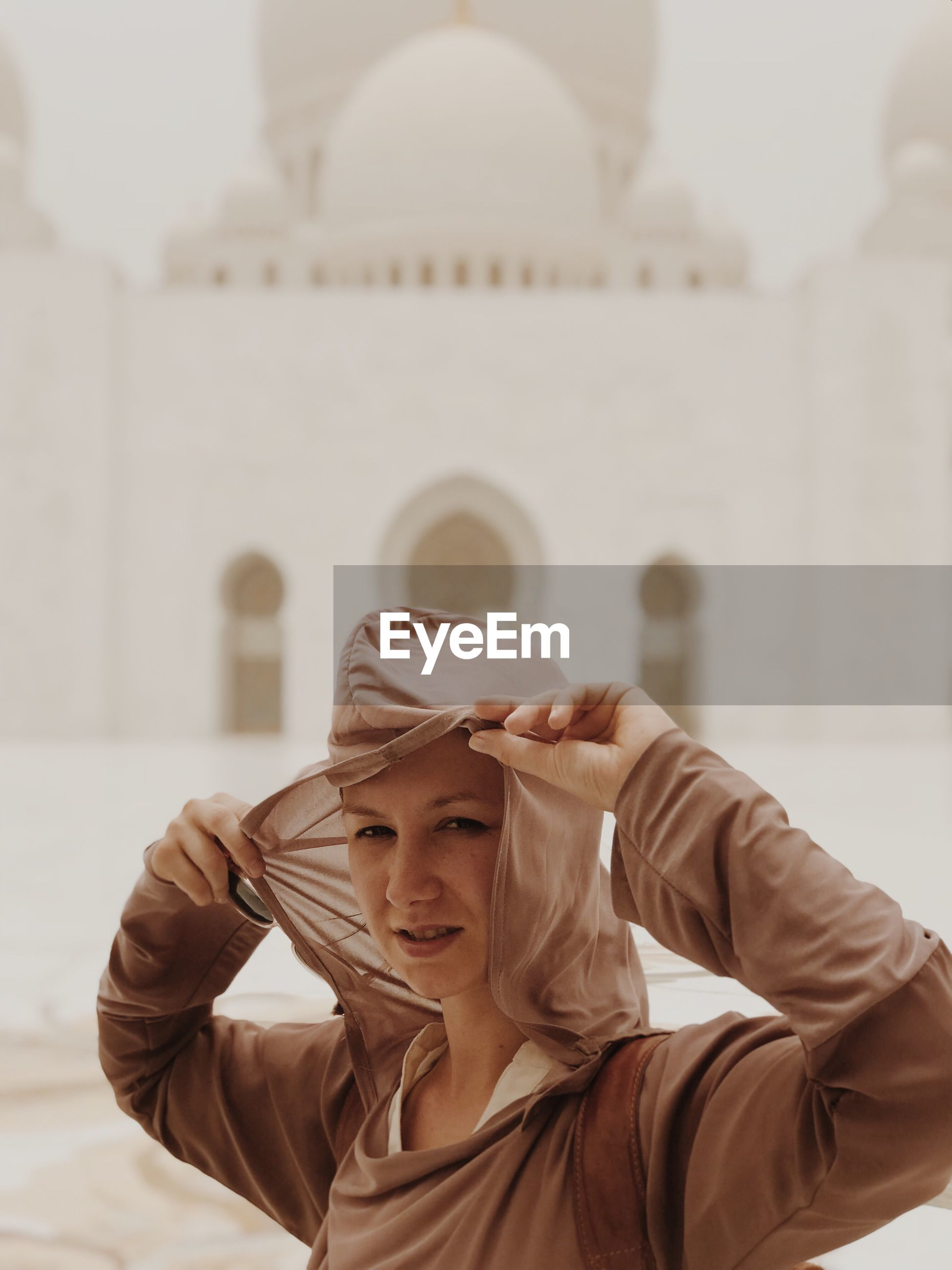 one person, portrait, headshot, clothing, lifestyles, focus on foreground, front view, architecture, real people, hat, young women, built structure, casual clothing, leisure activity, smiling, young adult, day, women, hairstyle