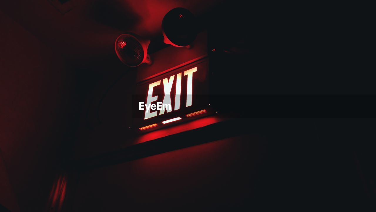 Low Angle View Of Illuminated Exit Sign On Wall In Dark