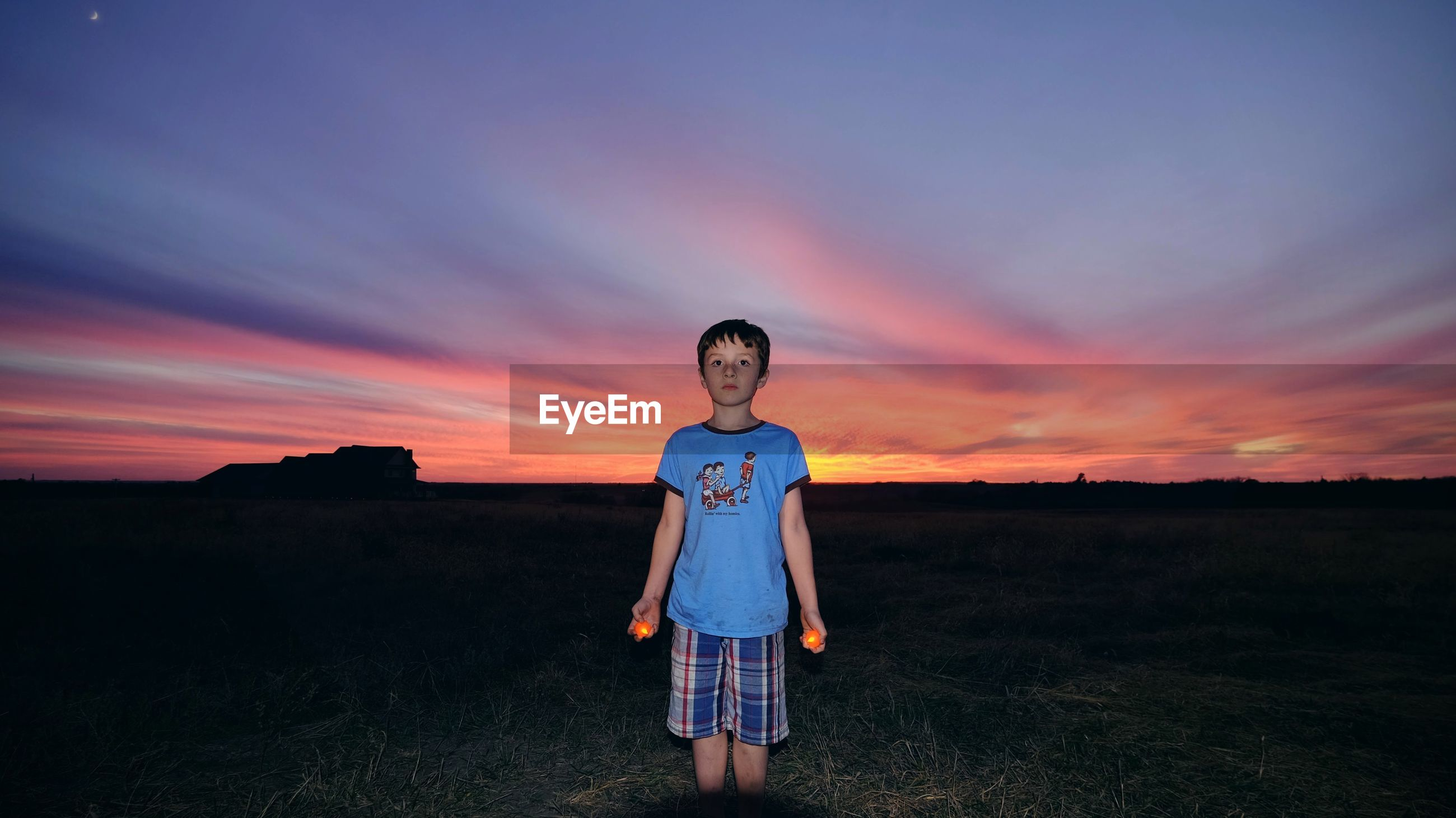 Boy holding lit candles while standing on grassy field at dusk
