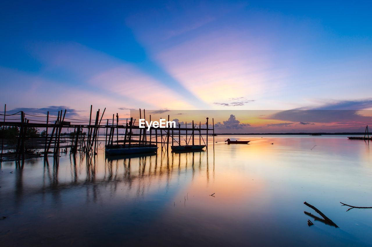 sky, sunset, water, reflection, scenics, beauty in nature, tranquil scene, nature, tranquility, sea, cloud - sky, outdoors, nautical vessel, no people, silhouette, transportation, built structure, moored, travel destinations, beach, architecture, day