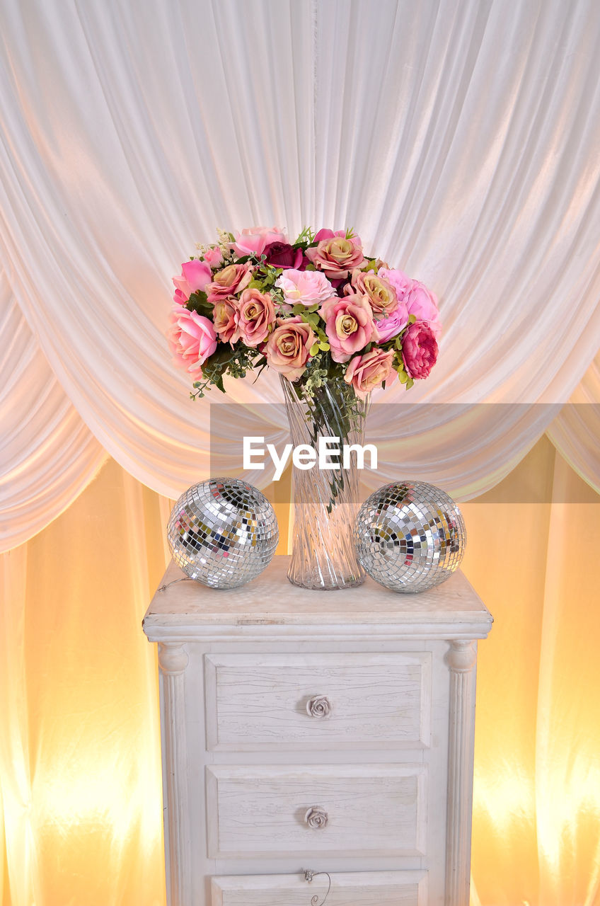 Flower Vase With Disco Balls On Table Against Curtain
