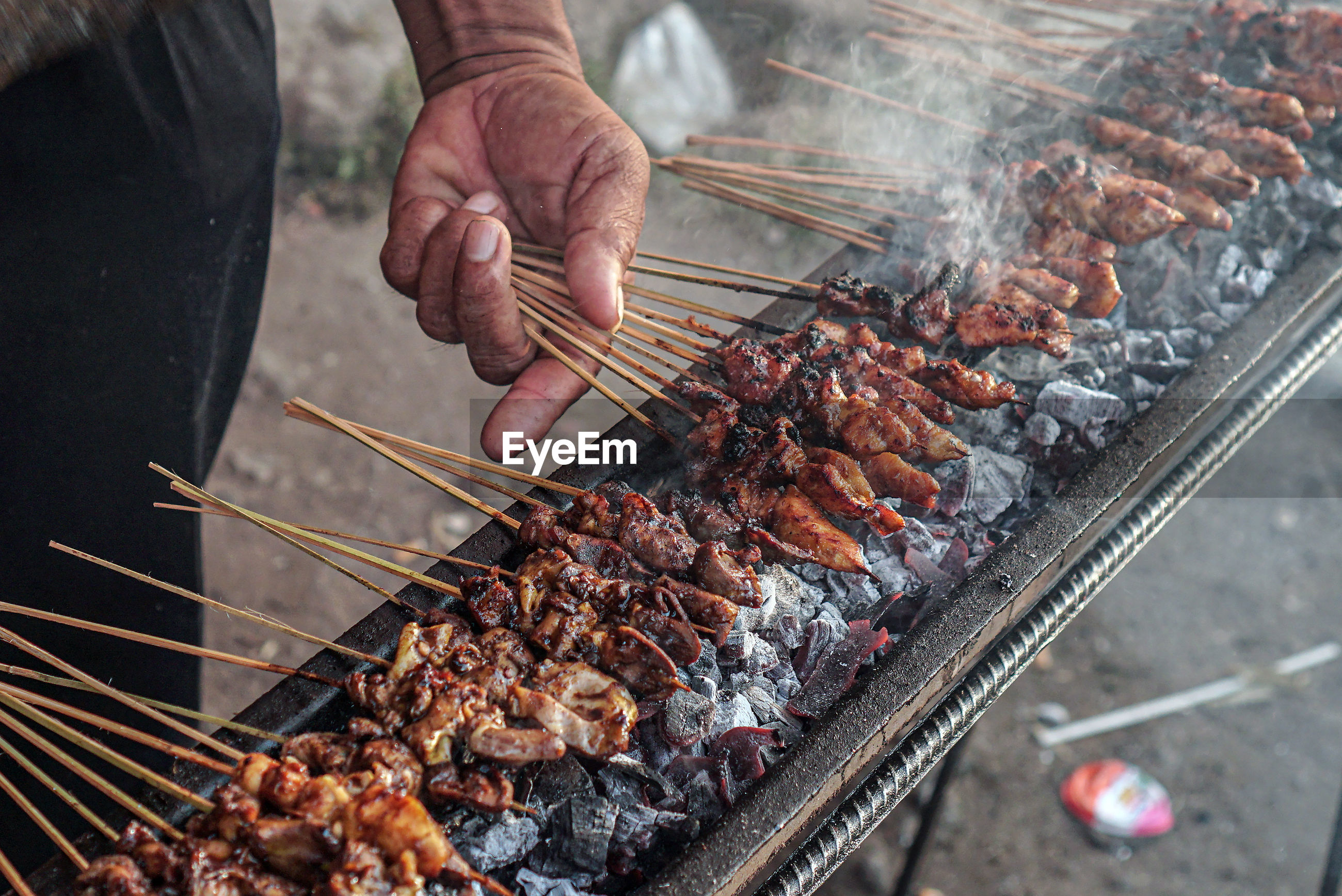 MIDSECTION OF MAN PREPARING FOOD ON BARBECUE