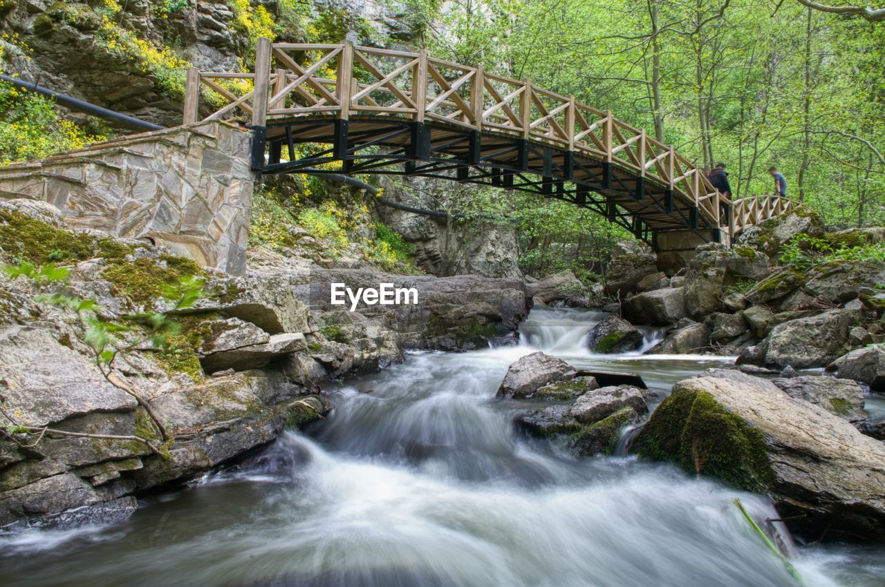 water, bridge, connection, flowing water, rock, motion, bridge - man made structure, scenics - nature, rock - object, tree, forest, beauty in nature, long exposure, solid, nature, plant, no people, river, waterfall, flowing, stream - flowing water, outdoors, footbridge, power in nature