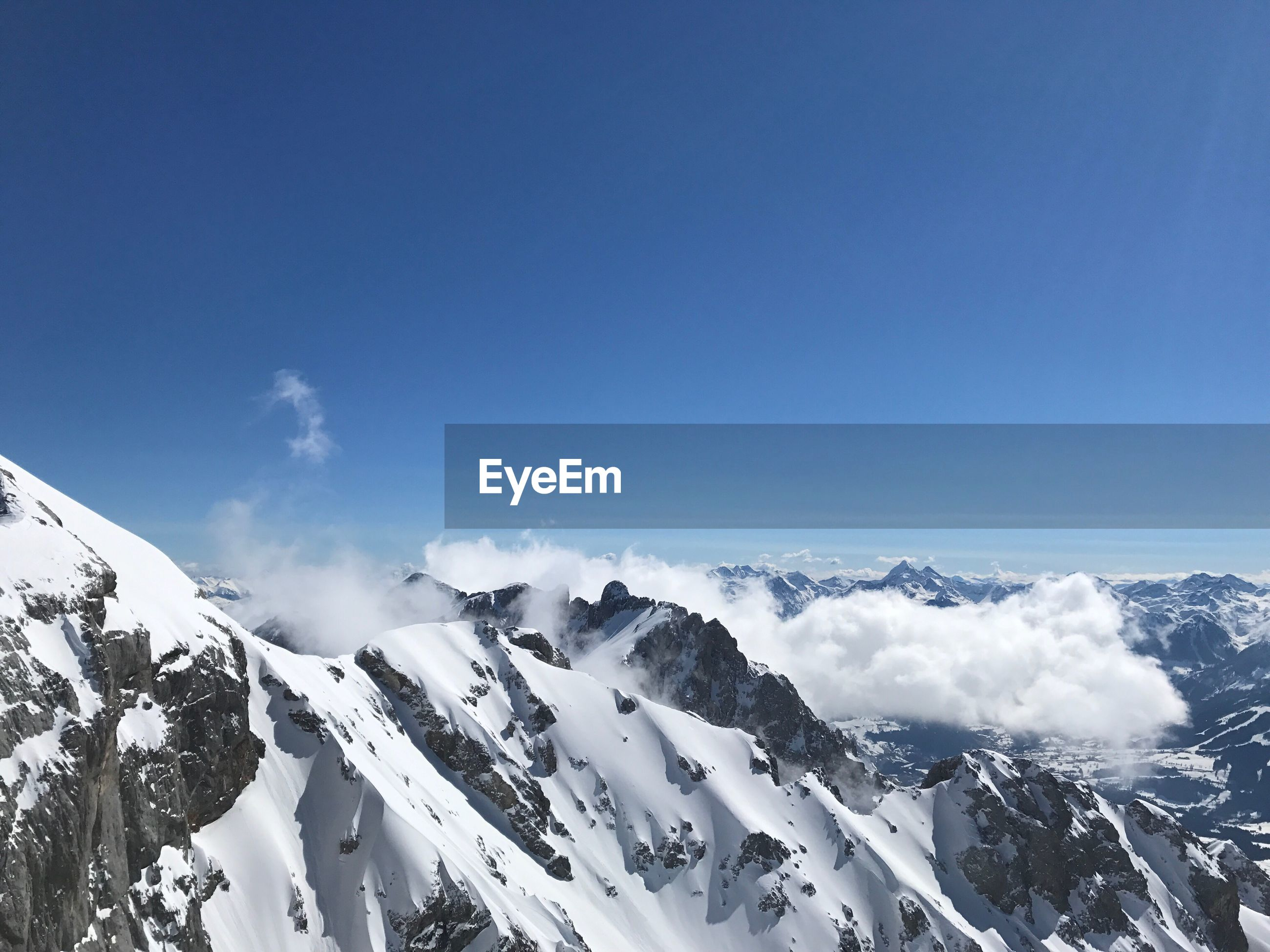 Snowcapped mountains against blue sky during winter