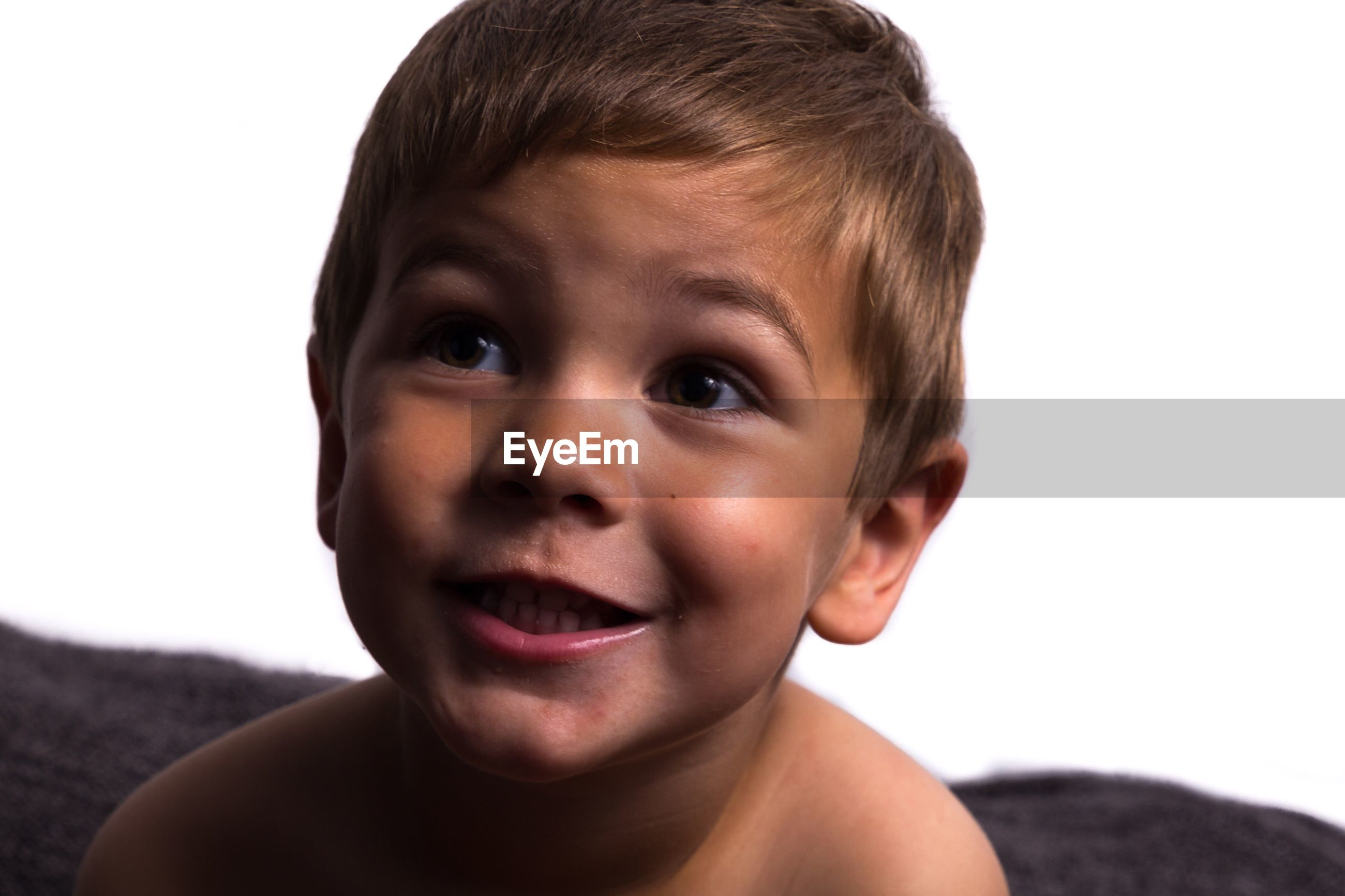 Close-up of shirtless boy looking away against white background