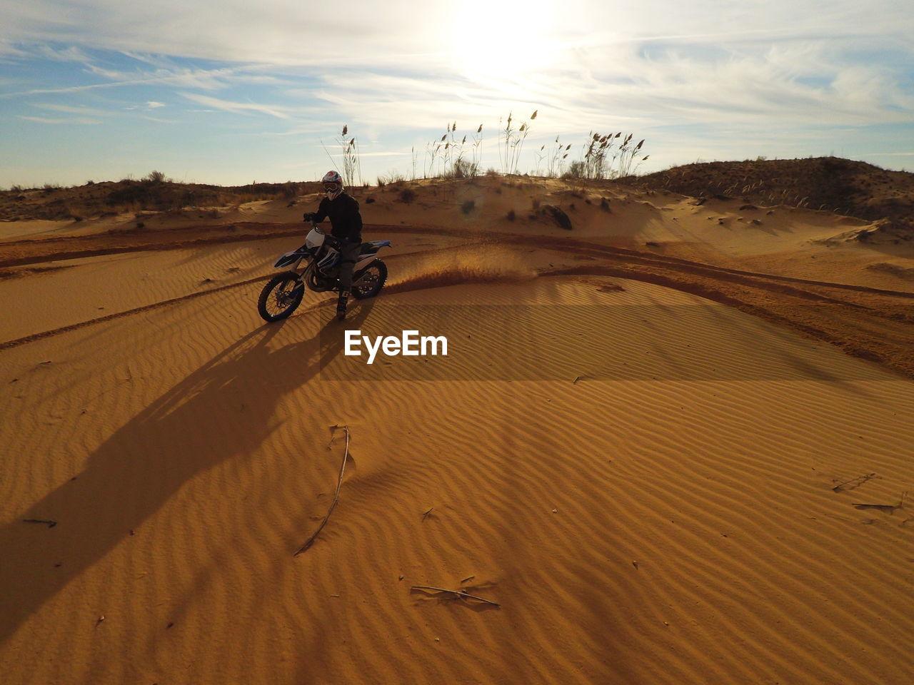 MAN CYCLING IN DESERT