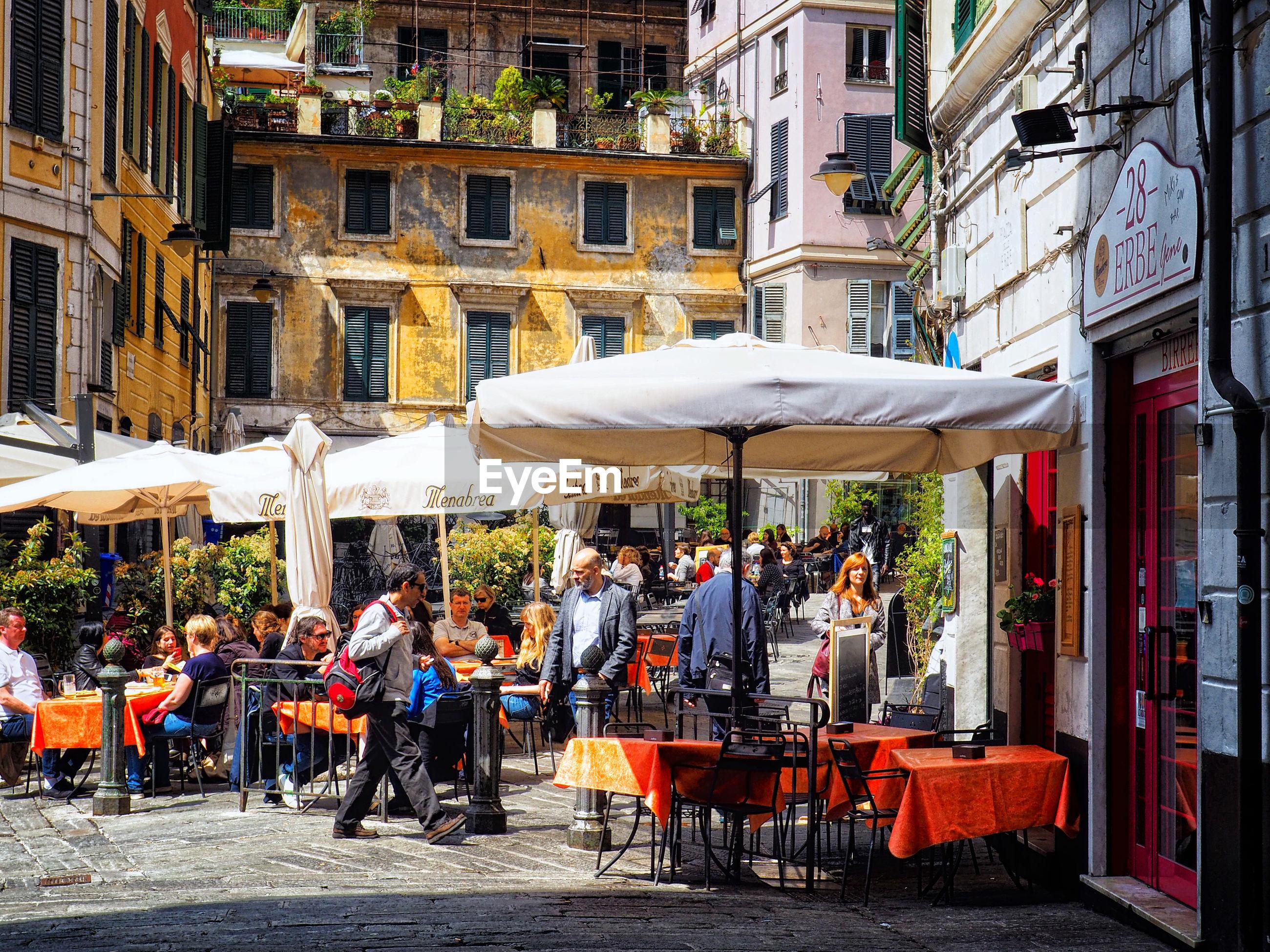PEOPLE AT SIDEWALK CAFE BY BUILDINGS