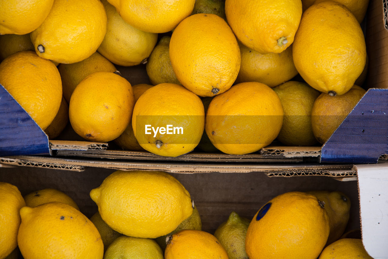 healthy eating, food and drink, food, wellbeing, fruit, freshness, yellow, citrus fruit, market, retail, for sale, large group of objects, abundance, still life, box, container, orange color, high angle view, day, orange, no people, box - container, retail display, ripe