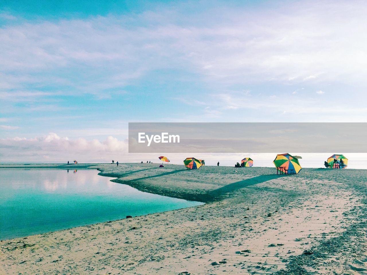 Umbrellas At Beach Against Sky