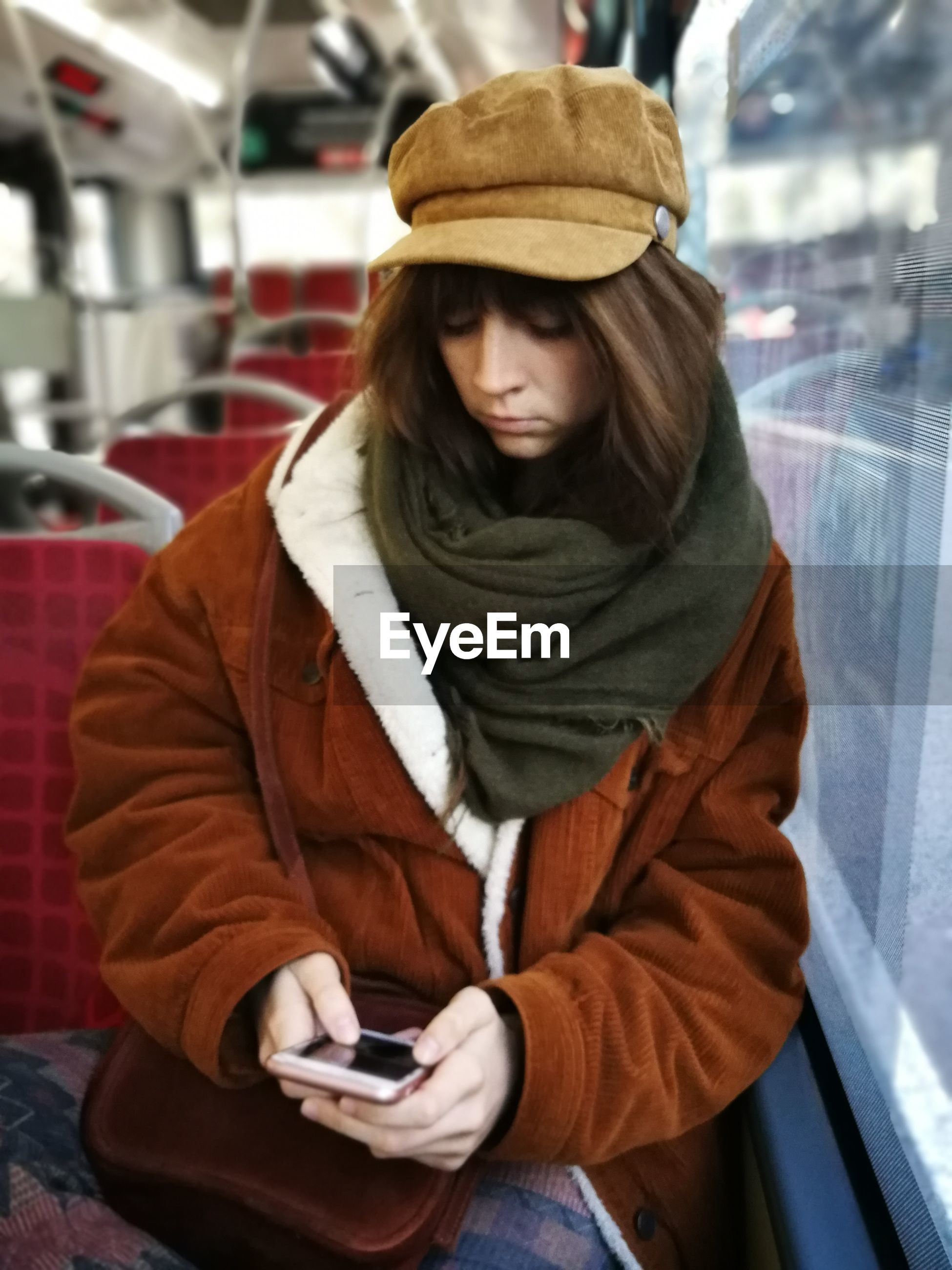 Young woman wearing warm clothing while using mobile phone in bus