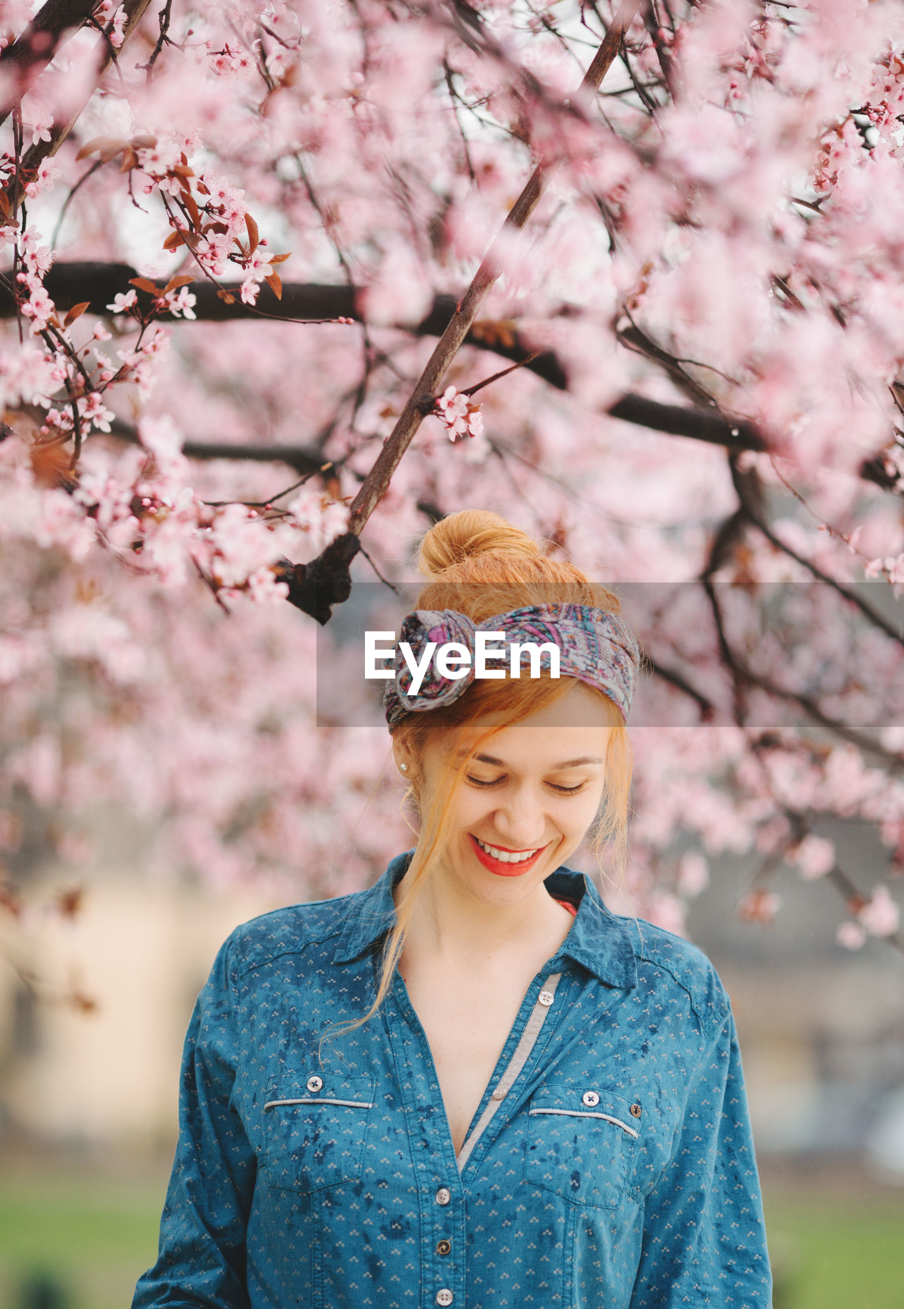 PORTRAIT OF SMILING YOUNG WOMAN WITH PINK CHERRY BLOSSOMS