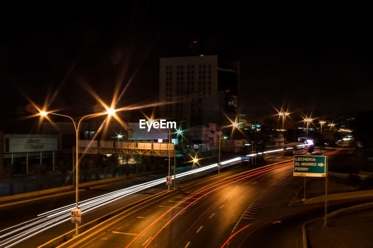 illuminated, night, light trail, speed, transportation, long exposure, motion, high street, architecture, no people, building exterior, road, built structure, outdoors, city, sky