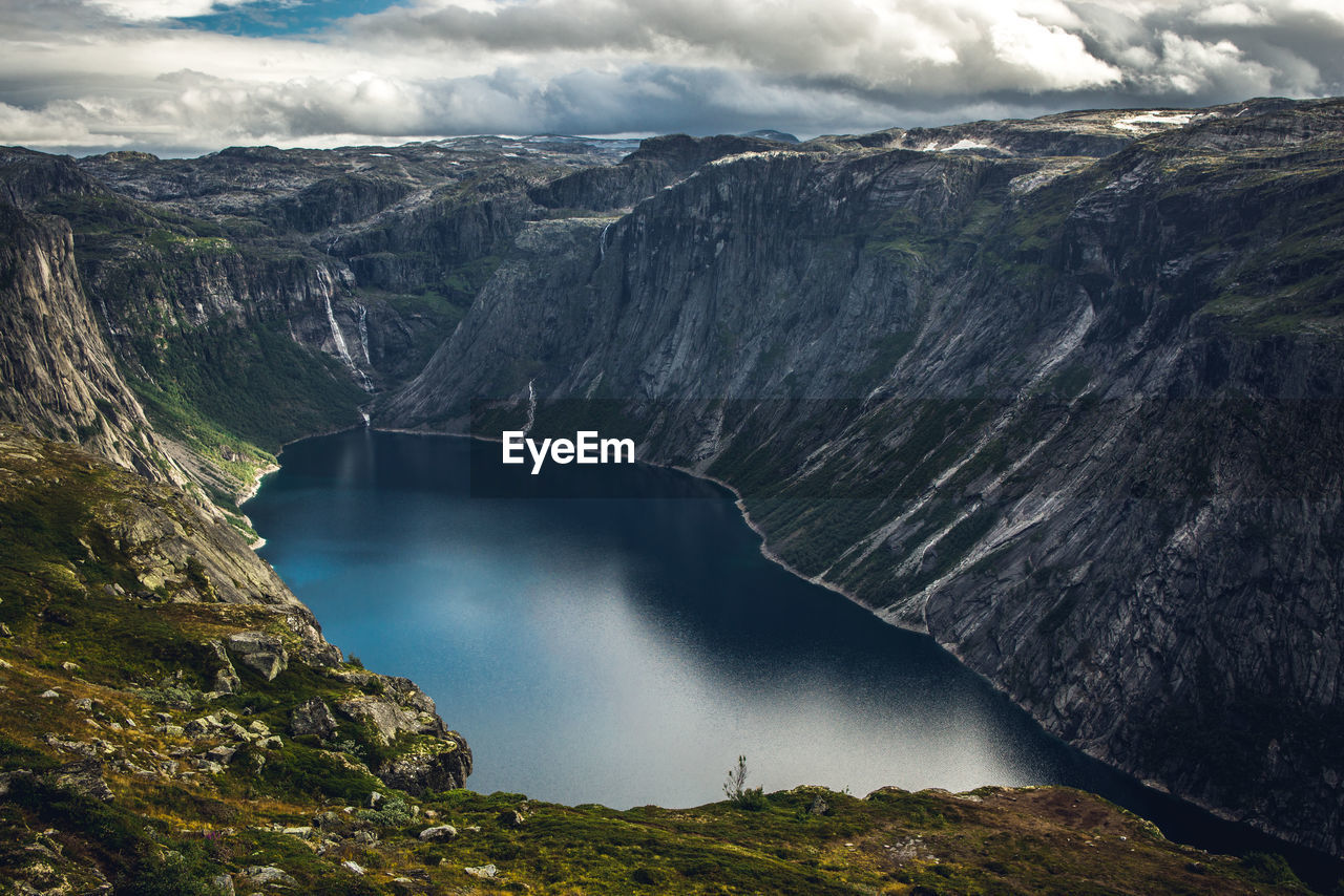 Aerial view of lake by mountain against sky