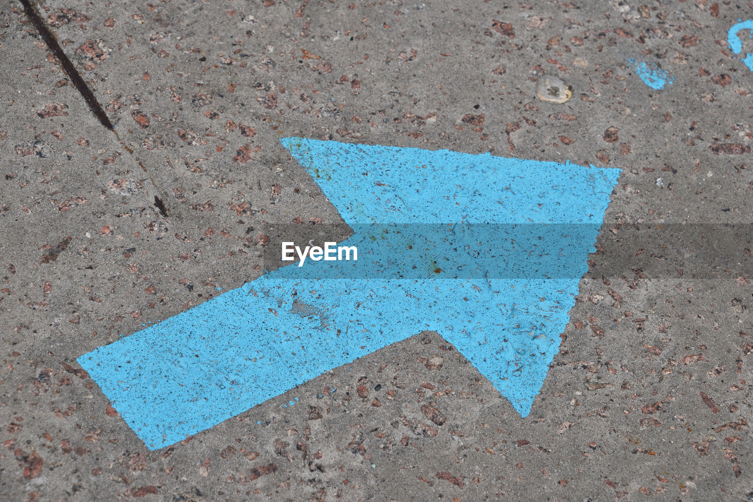 Detail shot of arrow sign on ground