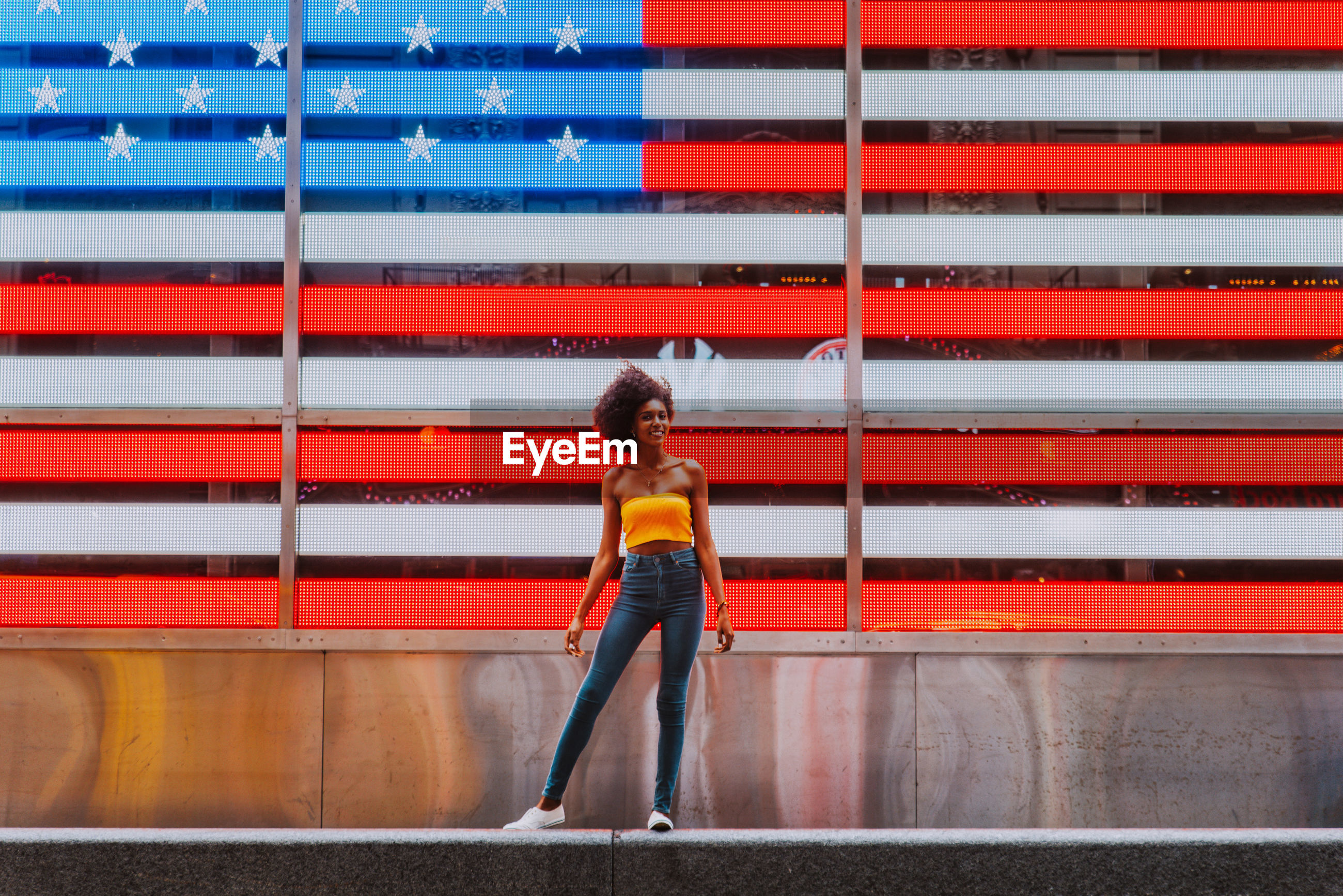 Full length portrait of happy young woman standing against neon american flag in city