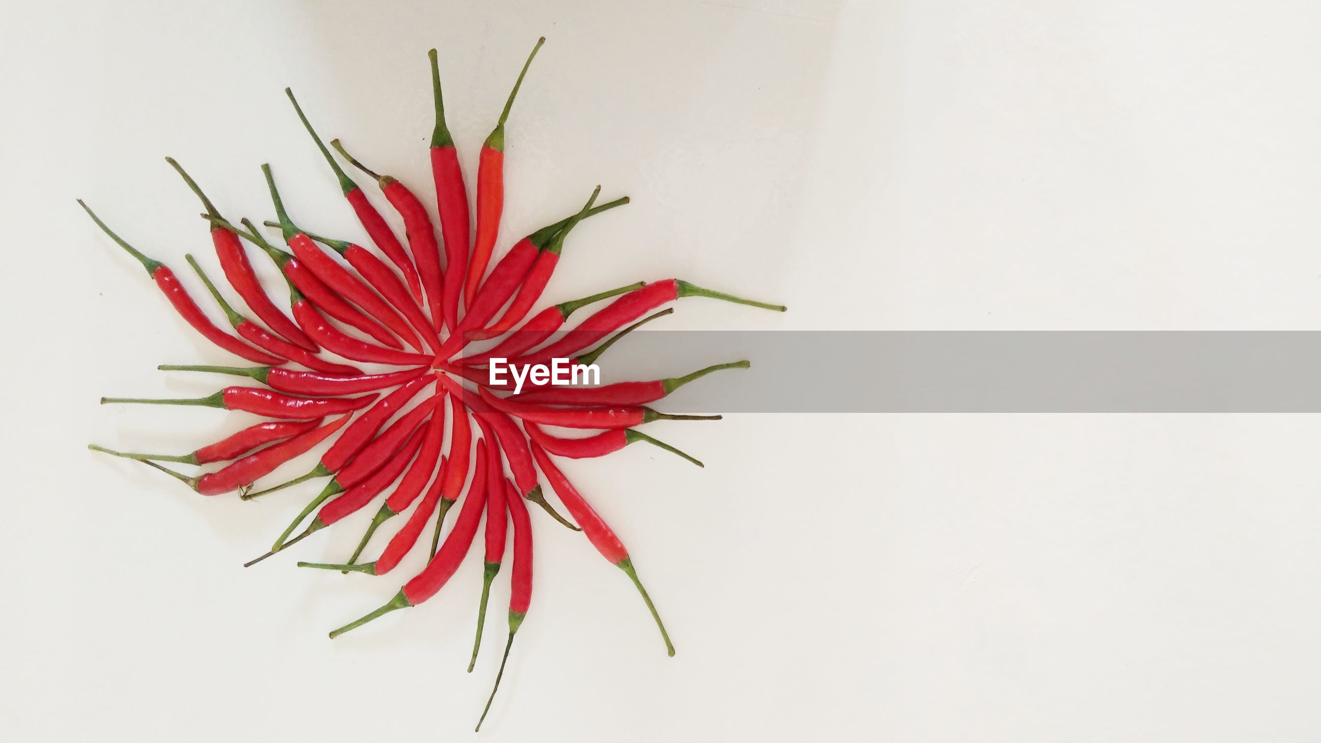 CLOSE-UP OF RED CHILI PEPPER OVER WHITE BACKGROUND