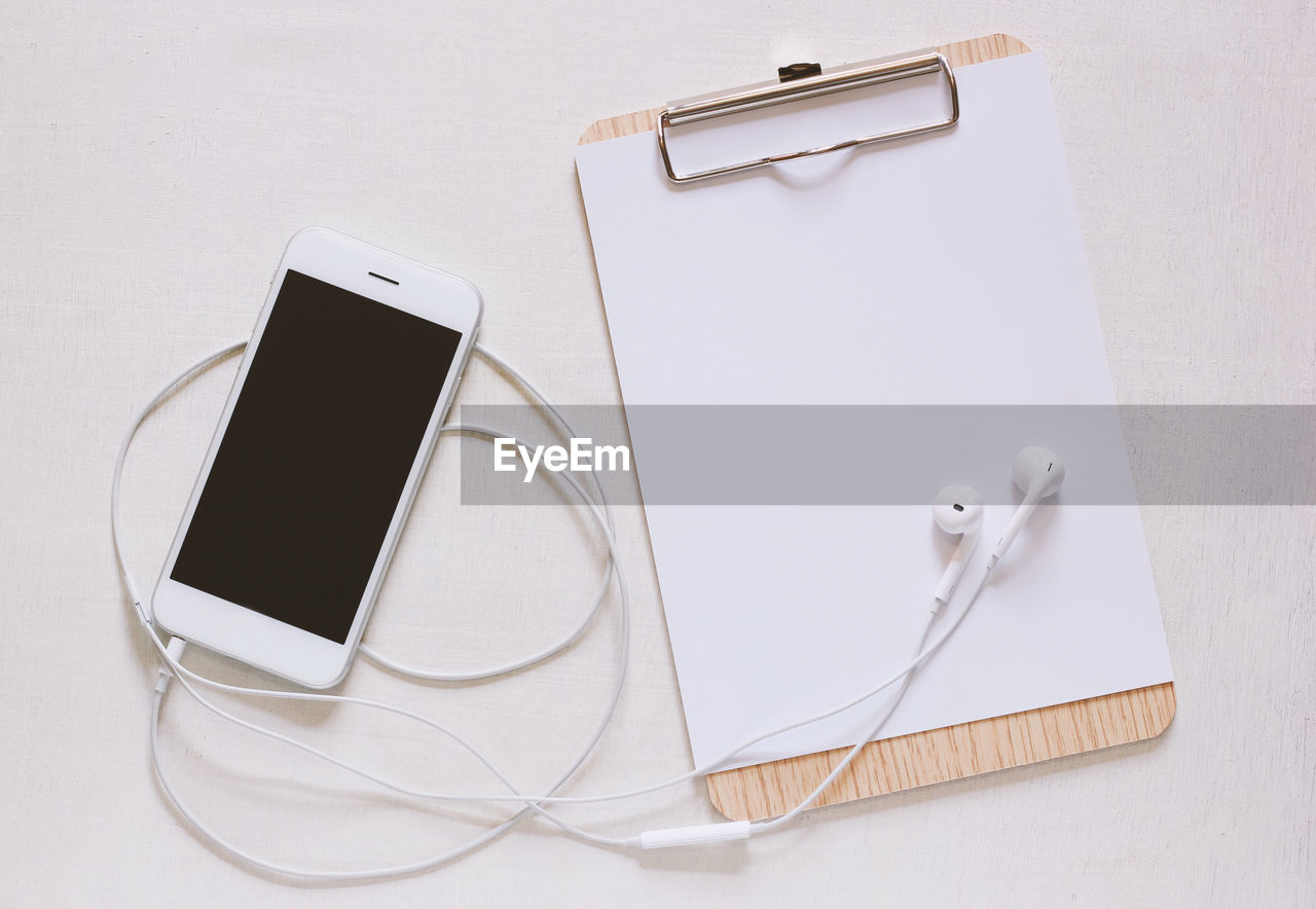 wireless technology, technology, connection, smart phone, portable information device, still life, communication, mobile phone, screen, telecommunications equipment, device screen, table, high angle view, indoors, no people, cable, portability, close-up, headphones, touch screen, blank, personal accessory, hands-free device, power supply