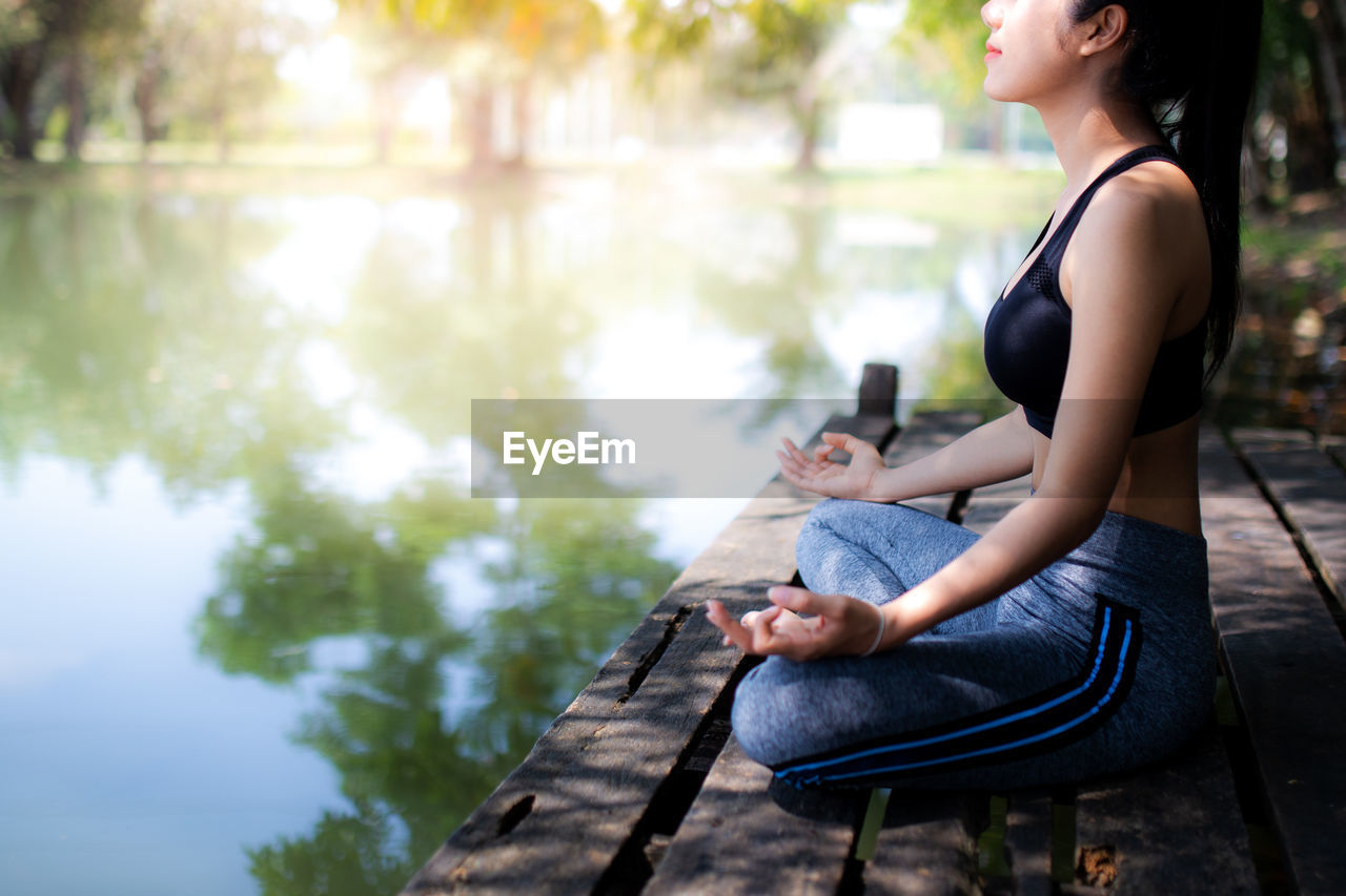 Side view of woman doing yoga while sitting by lake