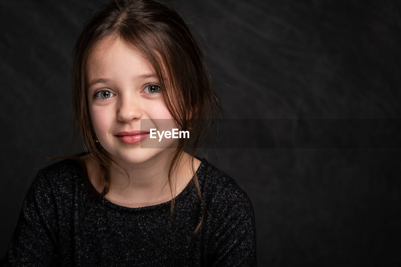 portrait, looking at camera, front view, headshot, child, indoors, childhood, one person, lifestyles, women, girls, smiling, females, casual clothing, studio shot, innocence, close-up, black background, hairstyle, human face