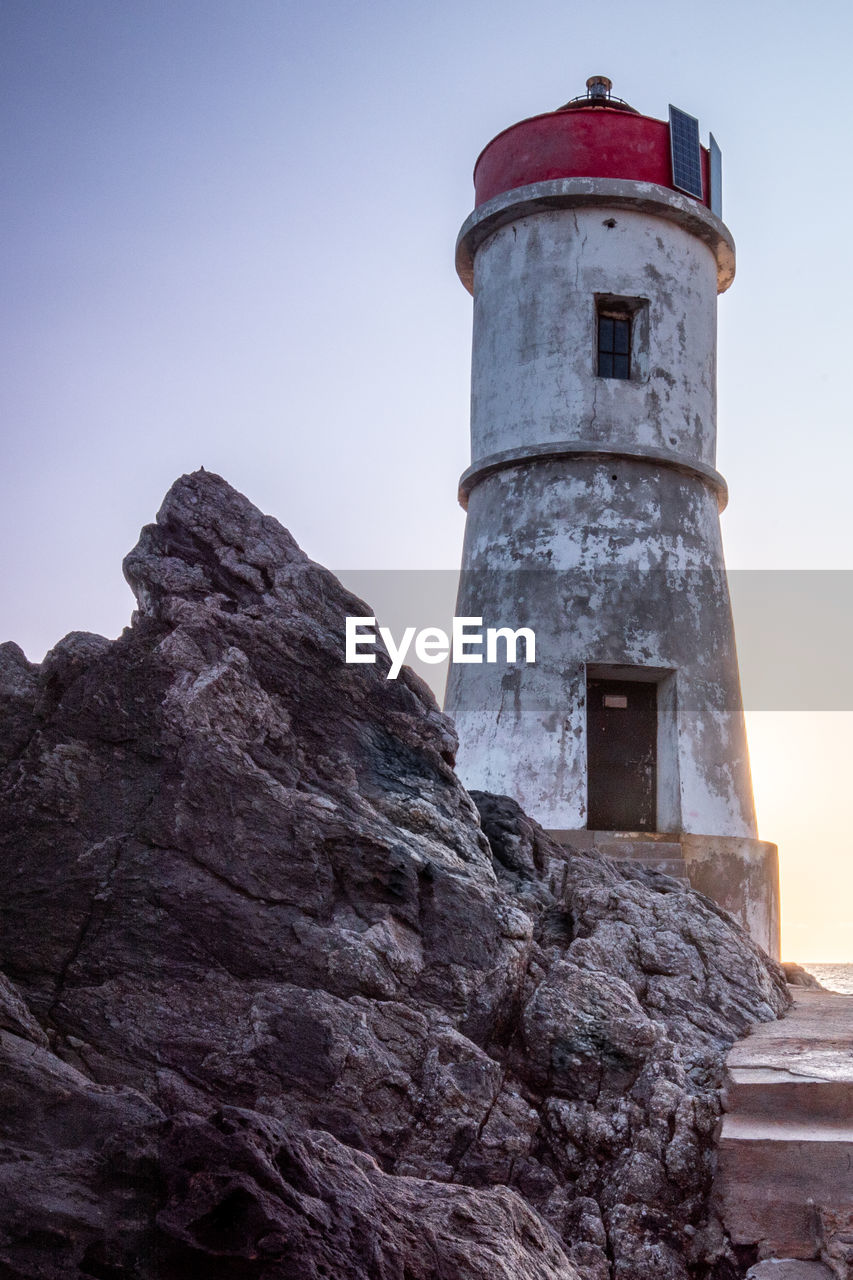 architecture, building exterior, built structure, sky, low angle view, clear sky, building, lighthouse, tower, guidance, nature, no people, rock, direction, day, protection, solid, outdoors, rock - object, history, stone wall
