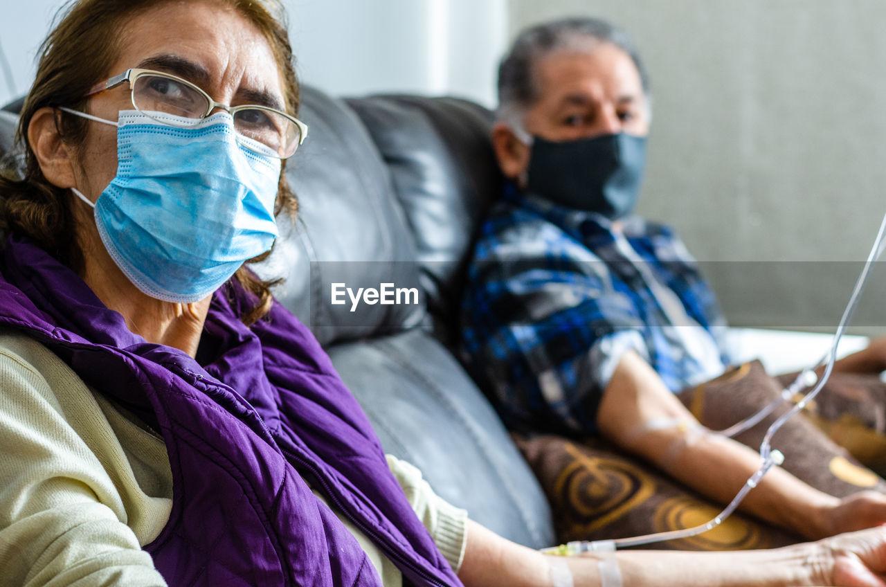 Senior couple wearing mask sitting at hospital
