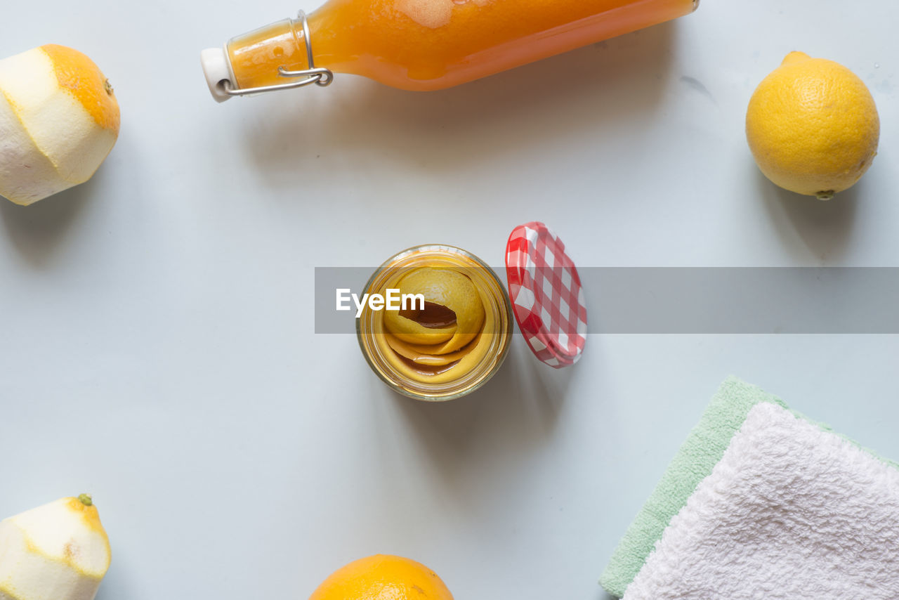 food, food and drink, indoors, still life, yellow, citrus fruit, table, wellbeing, healthy eating, fruit, orange color, no people, high angle view, freshness, orange - fruit, orange, lemon, close-up, directly above, white color, temptation