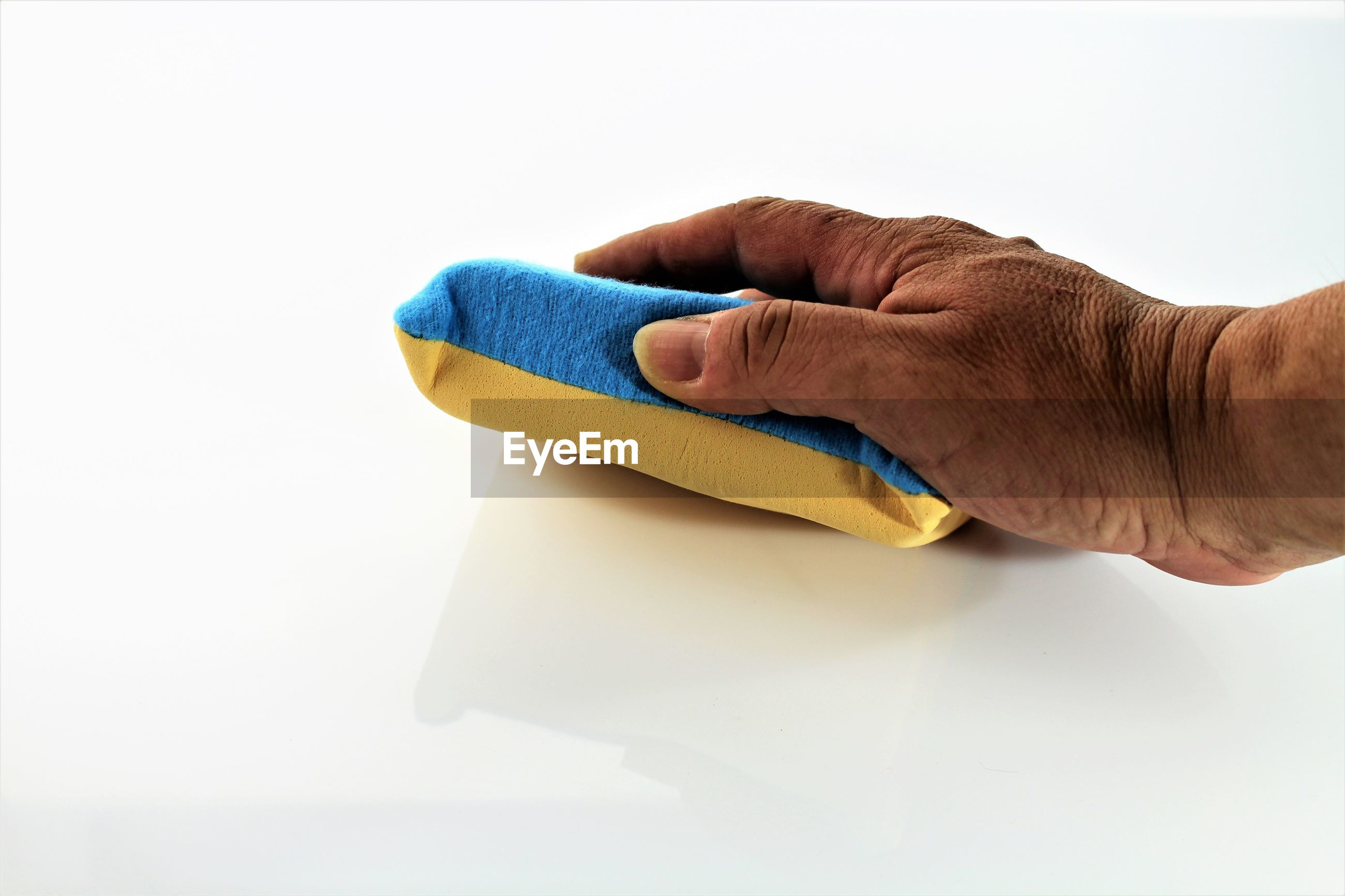 Cropped hand of person cleaning table with sponge