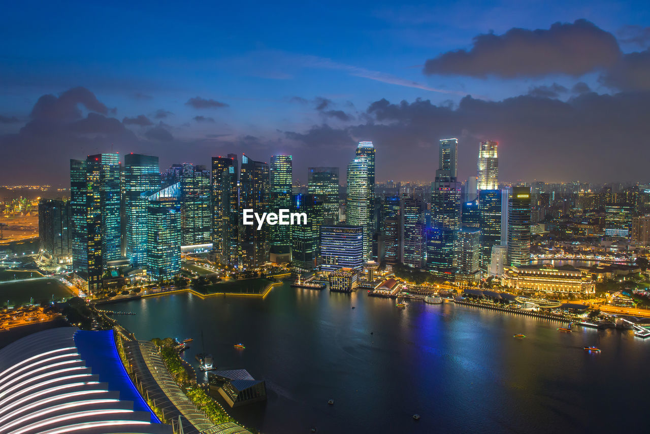 ILLUMINATED CITY BY RIVER AND BUILDINGS AGAINST SKY
