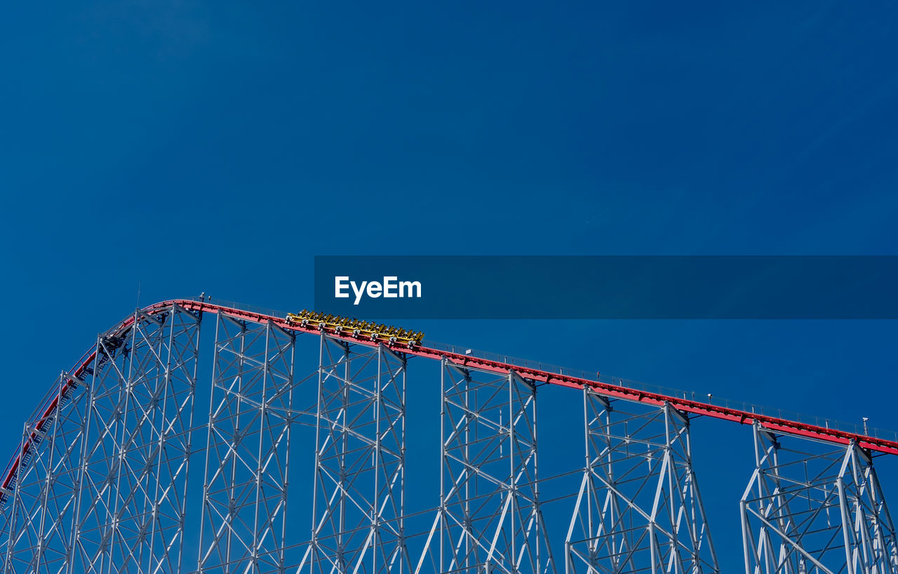 sky, blue, low angle view, nature, copy space, clear sky, arts culture and entertainment, architecture, amusement park ride, no people, built structure, metal, amusement park, day, rollercoaster, outdoors, travel, red, connection, excitement