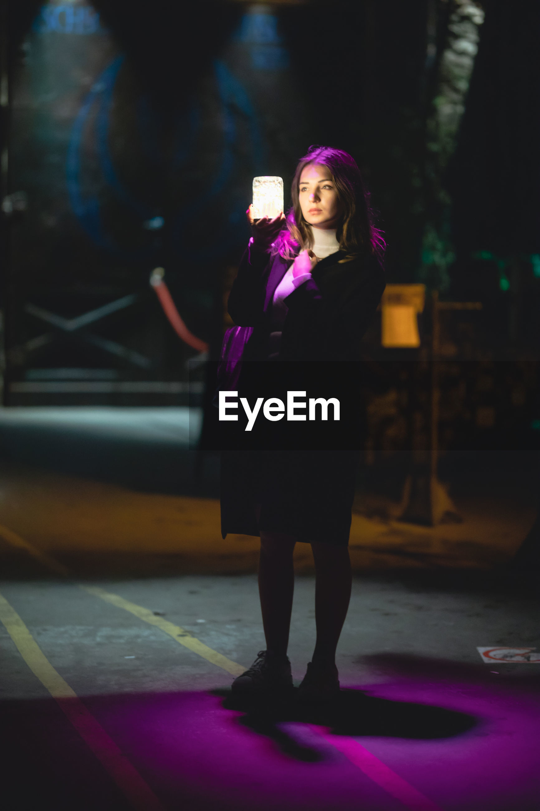 Full length of beautiful woman looking at glowing jar at night