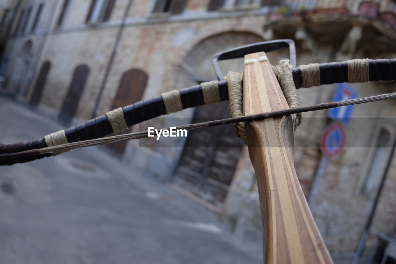 Close-Up Of Wooden Crossbow Against Buildings