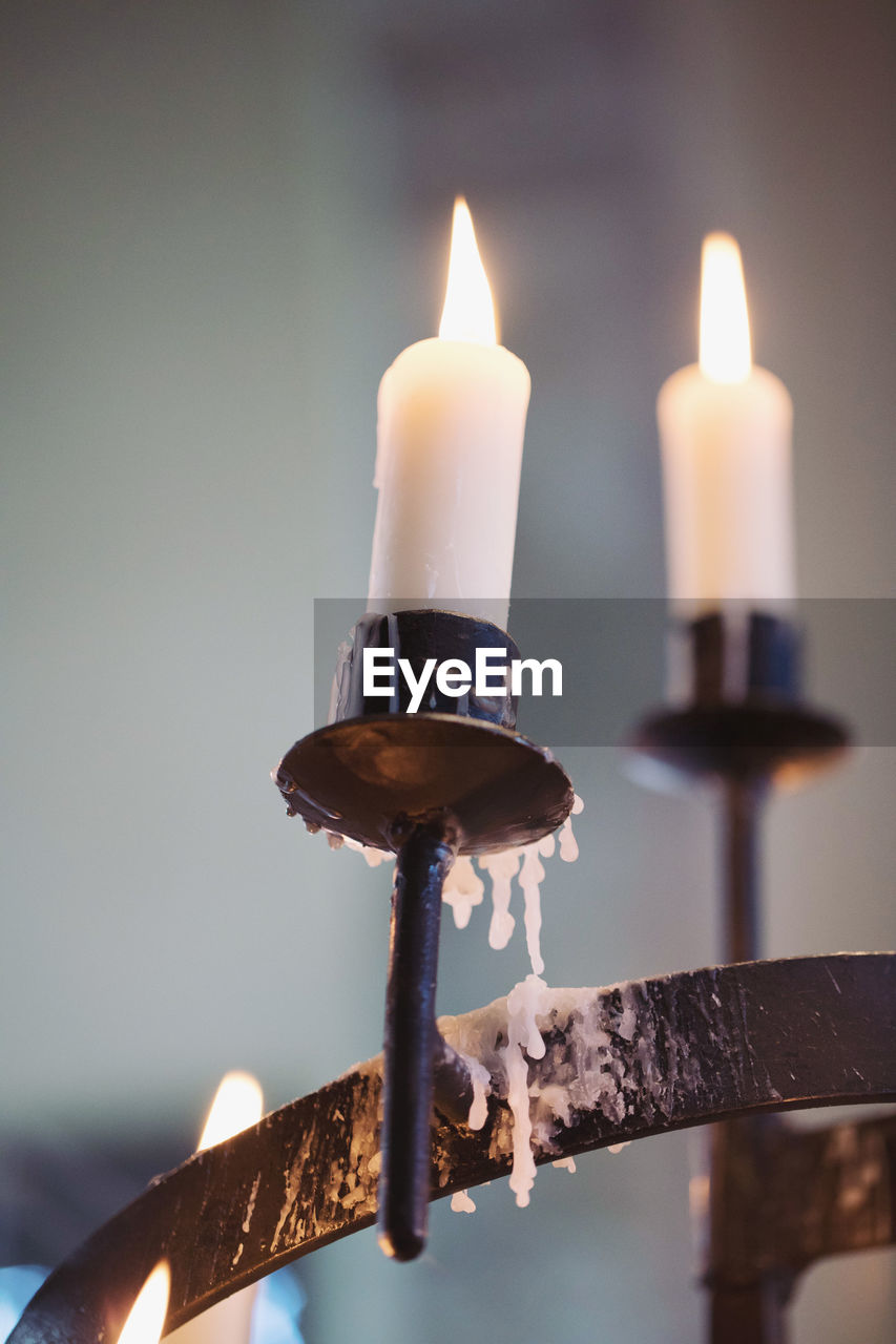 heat - temperature, flame, fire, burning, candle, illuminated, close-up, fire - natural phenomenon, metal, focus on foreground, no people, nature, lighting equipment, glowing, selective focus, candlestick holder, indoors, melting, wax