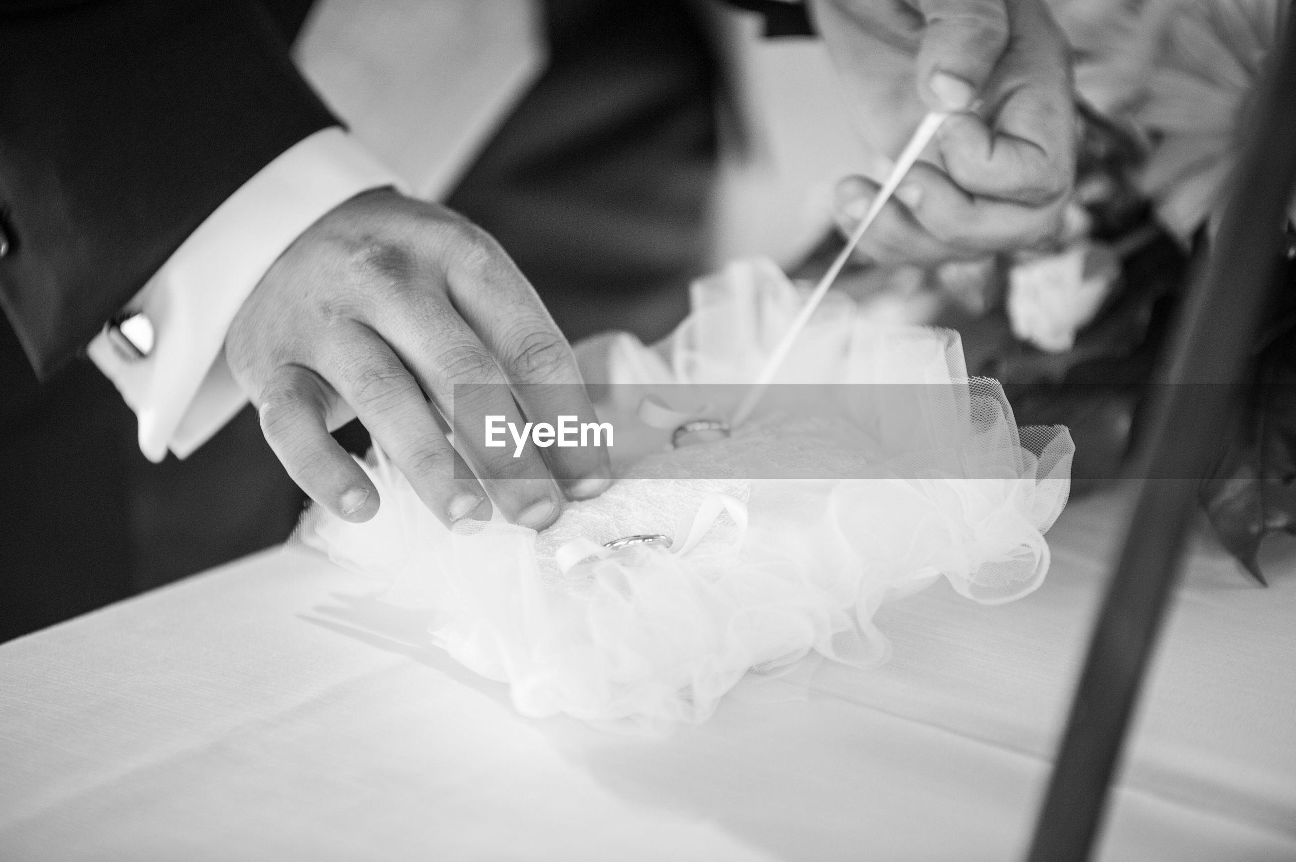 Cropped image of bridegroom taking wedding ring