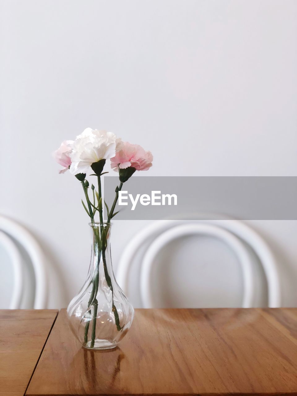 flower, flowering plant, table, plant, vase, indoors, fragility, vulnerability, beauty in nature, nature, no people, freshness, wood - material, close-up, petal, flower head, glass - material, rose, decoration, pink color, flower arrangement, purple
