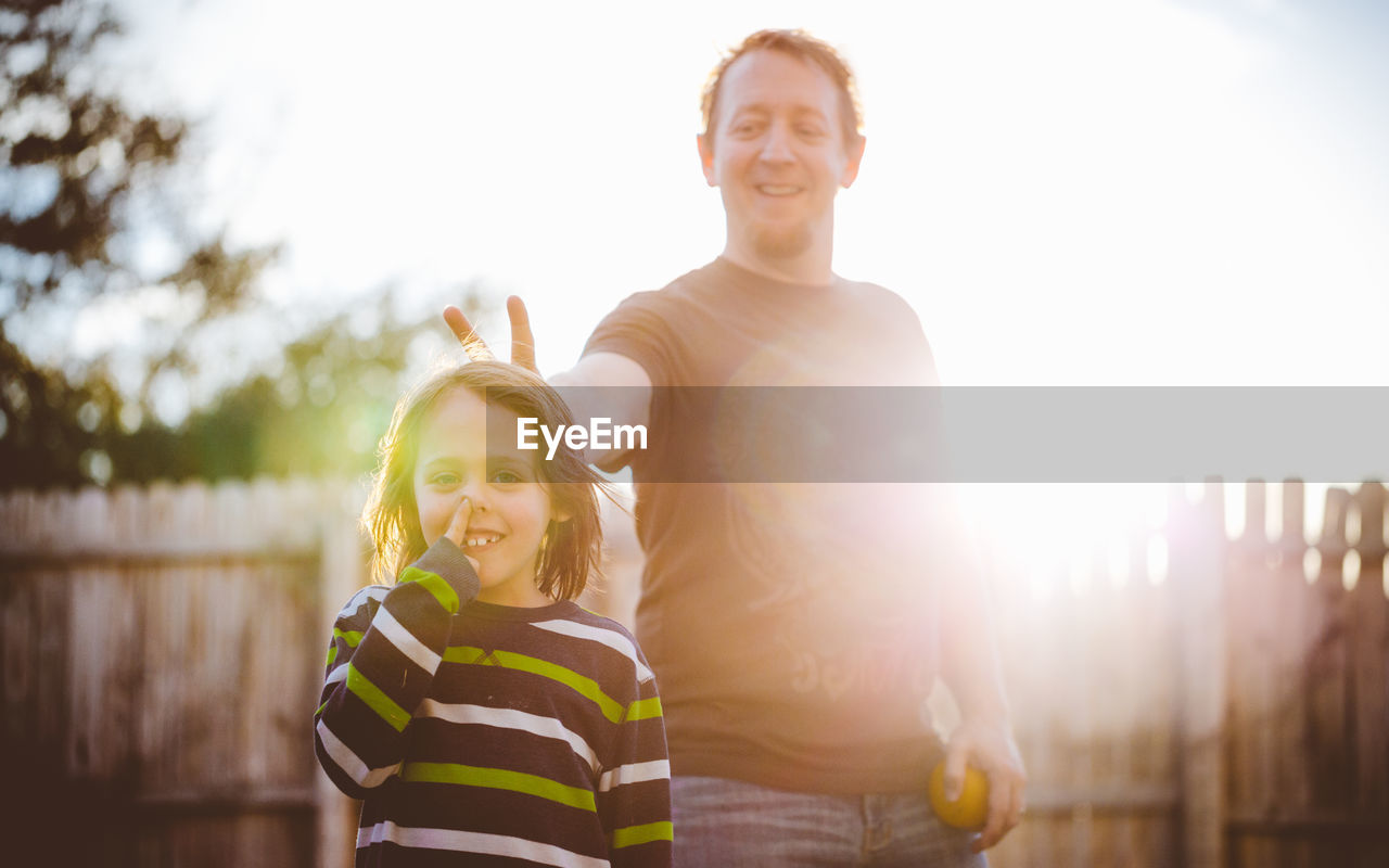 Smiling father making peace sign behind son in yard on sunny day