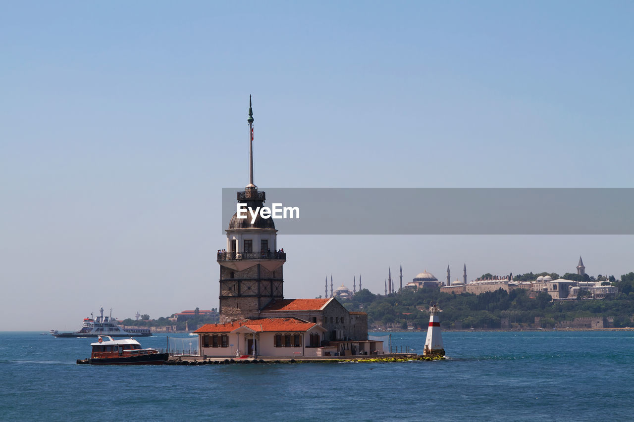 sky, architecture, built structure, water, nautical vessel, building exterior, waterfront, travel, transportation, nature, clear sky, tower, sea, building, copy space, religion, mode of transportation, no people, day, outdoors, passenger craft
