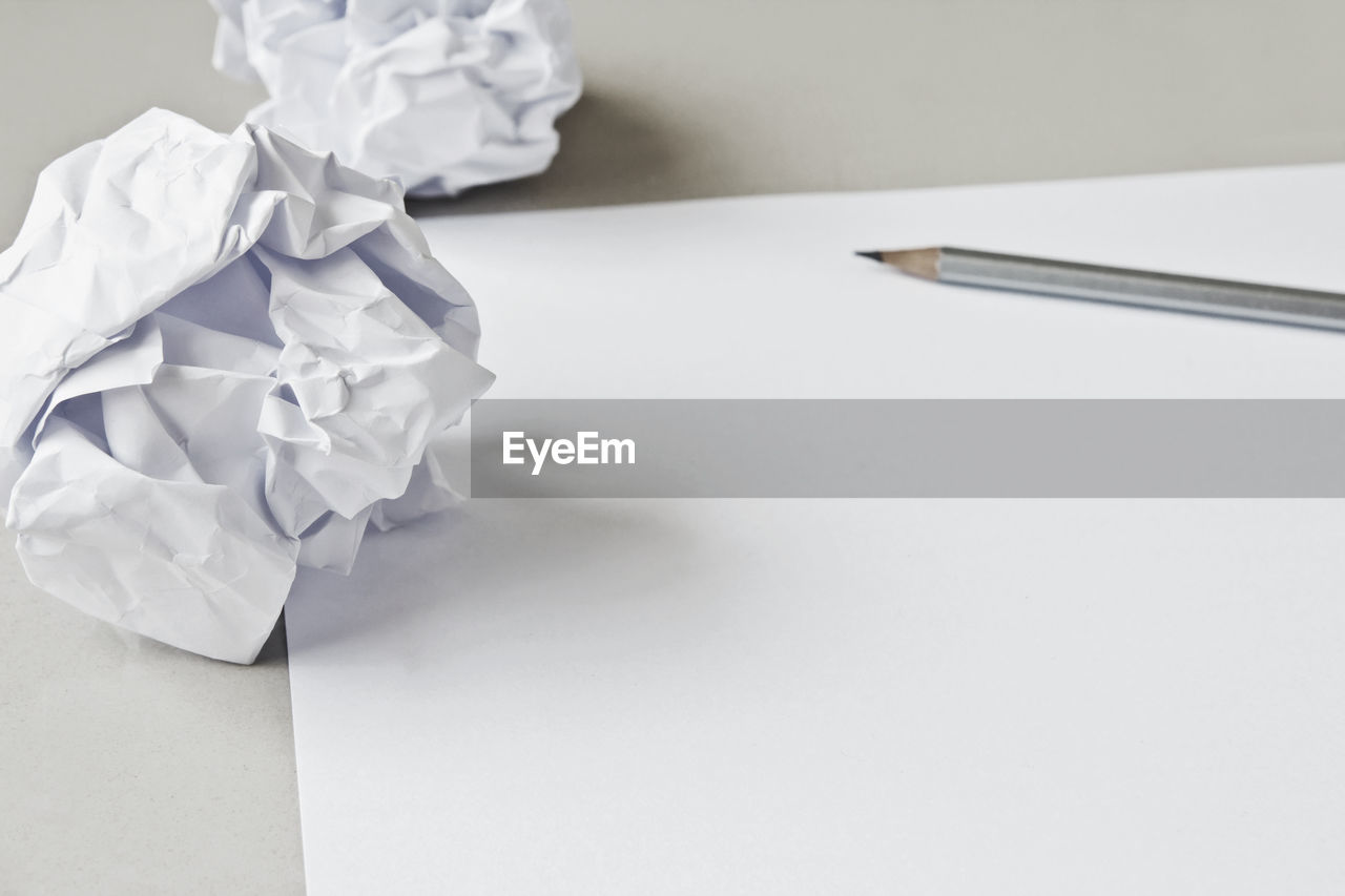 HIGH ANGLE VIEW OF WHITE PAPER ON TABLE AGAINST GRAY BACKGROUND