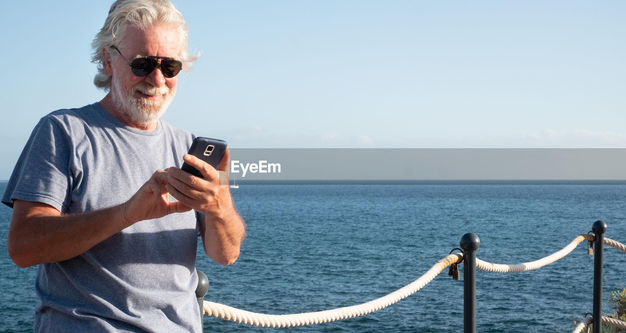 Smiling senior man using mobile phone while standing at sea