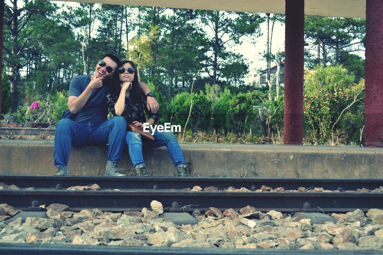 sitting, casual clothing, togetherness, railroad track, day, two people, full length, real people, young adult, tree, young women, smiling, outdoors, bonding, friendship, nature