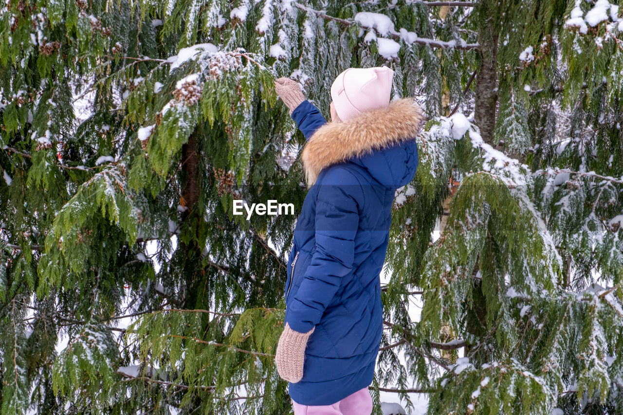 PERSON WEARING HAT AGAINST TREES IN WINTER