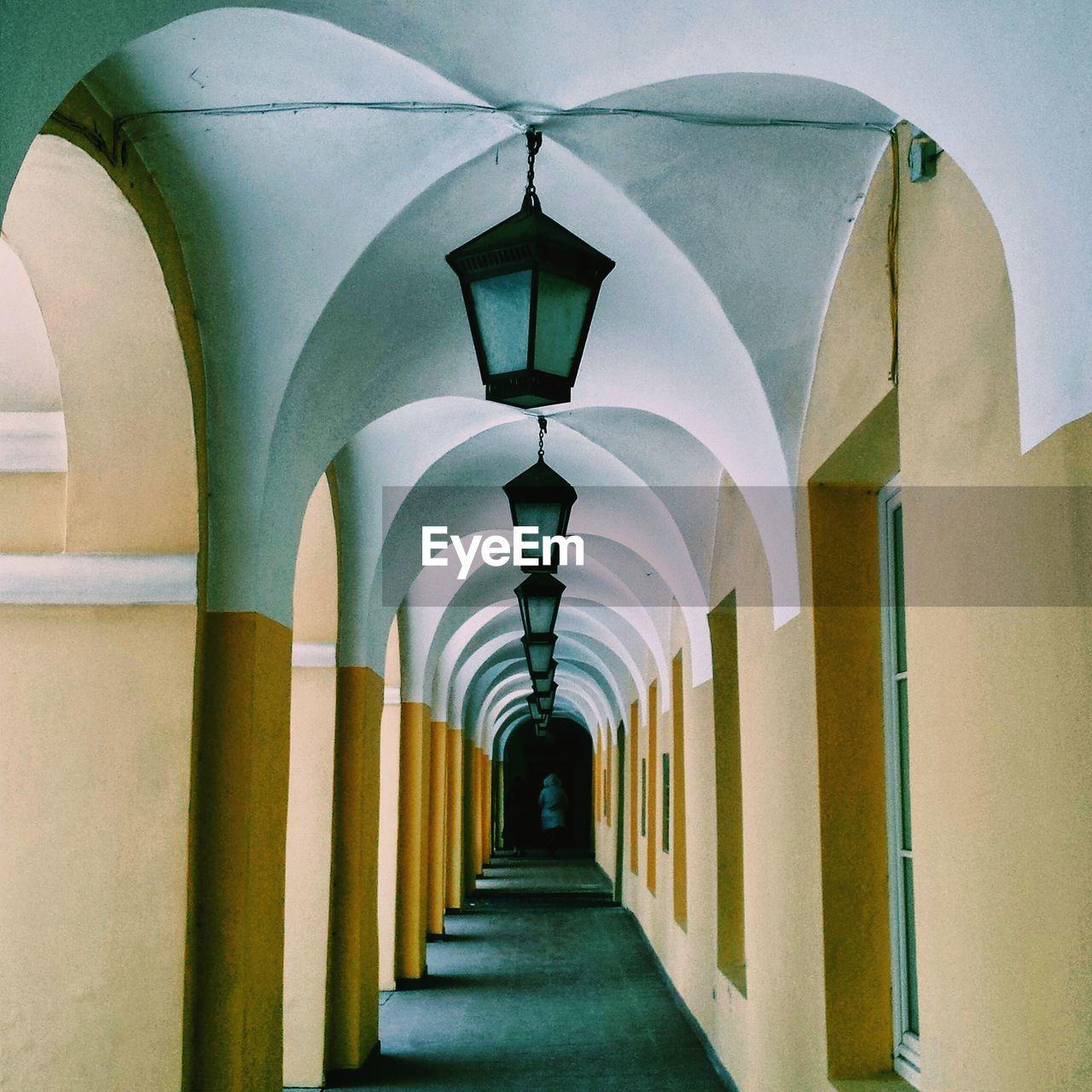 Hanging lights at narrow corridor along walls
